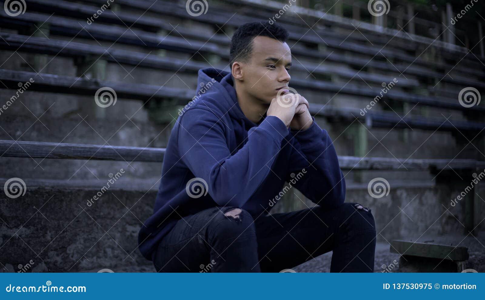 Adolescente afro-americano virado que senta-se na tribuna, na devastação e na pobreza ao redor