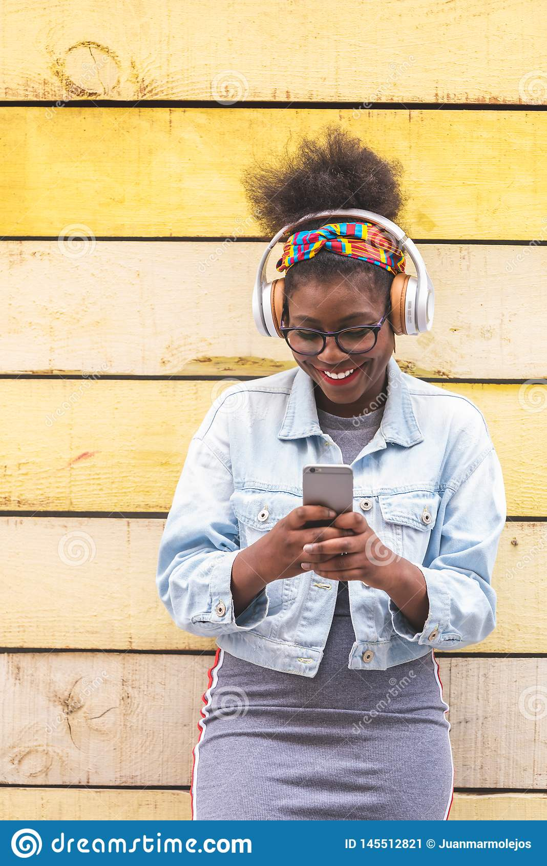 Adolescente afroamericano usando aire libre del teléfono móvil