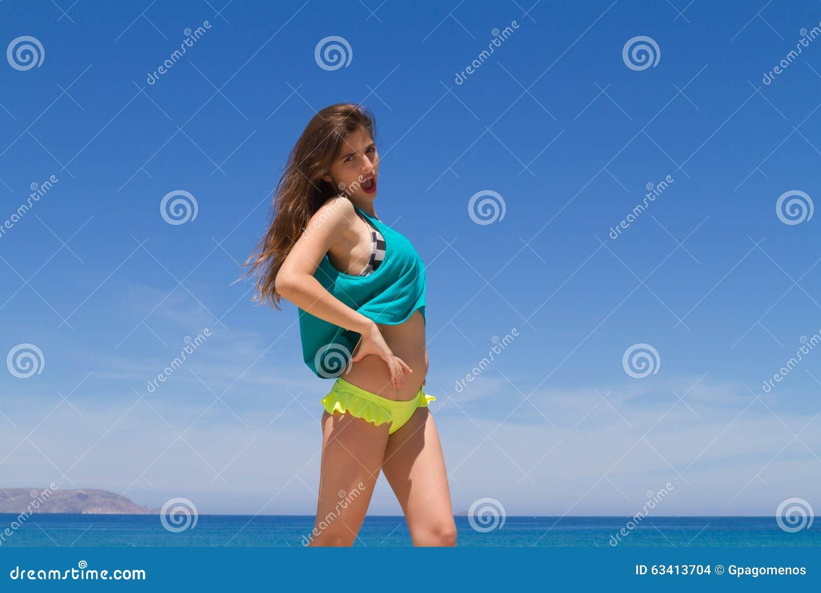 Adolescente alegre moreno en ropa de playa goza de