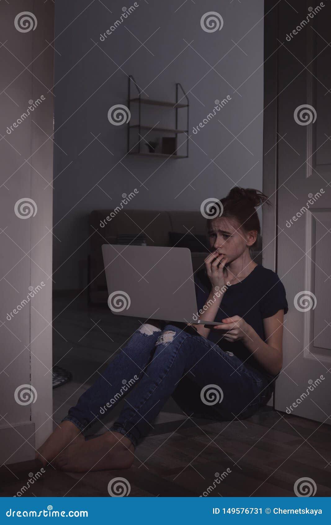 Adolescente amedrontado com o portátil no assoalho Perigo do Internet