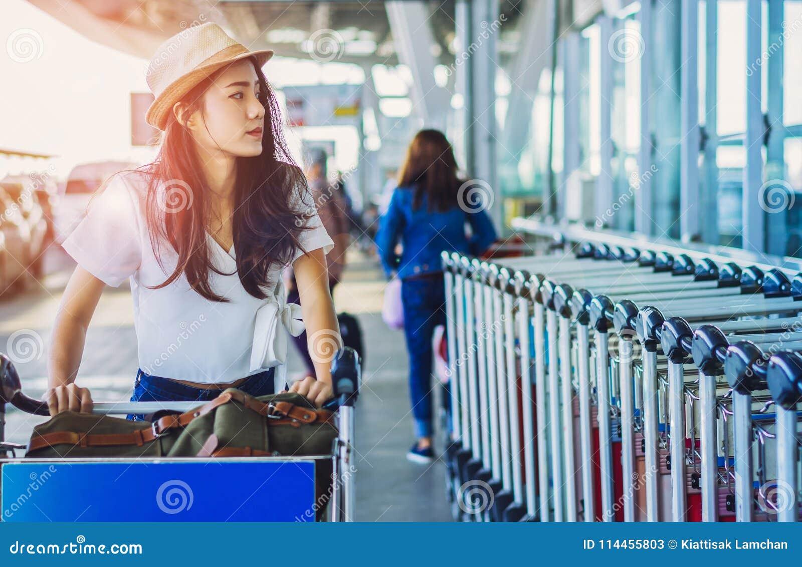 Adolescente asiático de la mujer con caminar del carro del equipaje