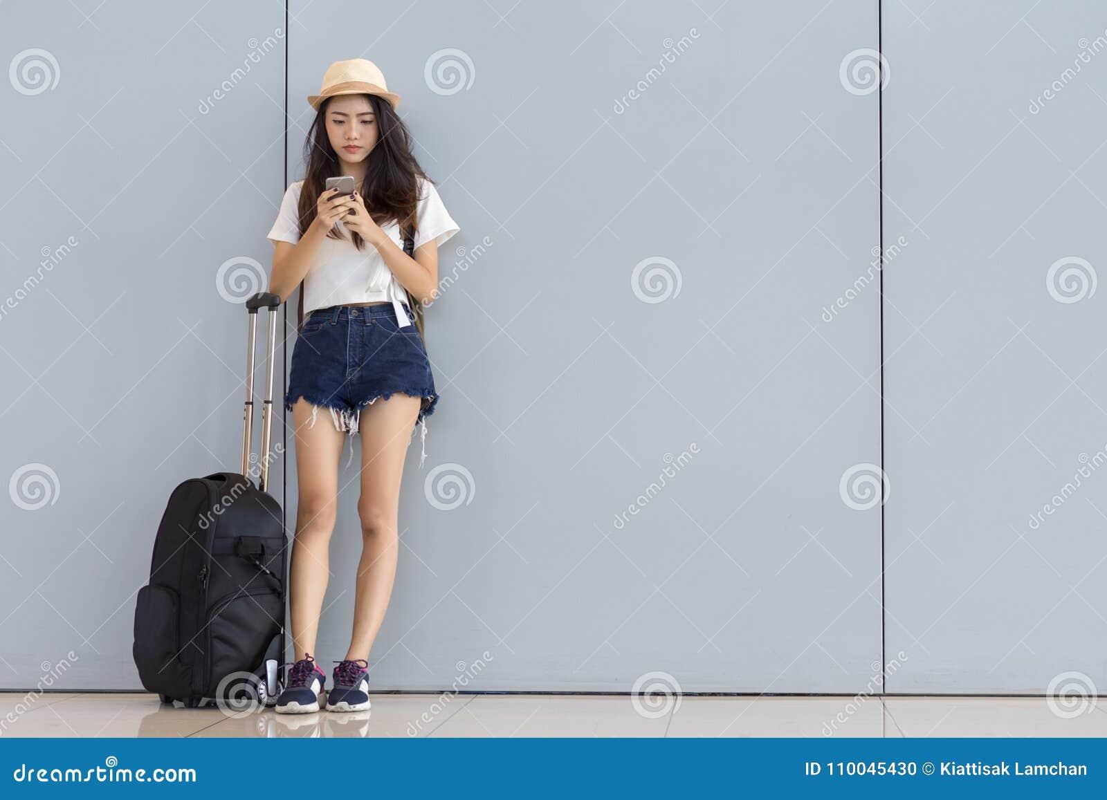 Adolescente asiático de la mujer que usa smartphone en el aeropuerto