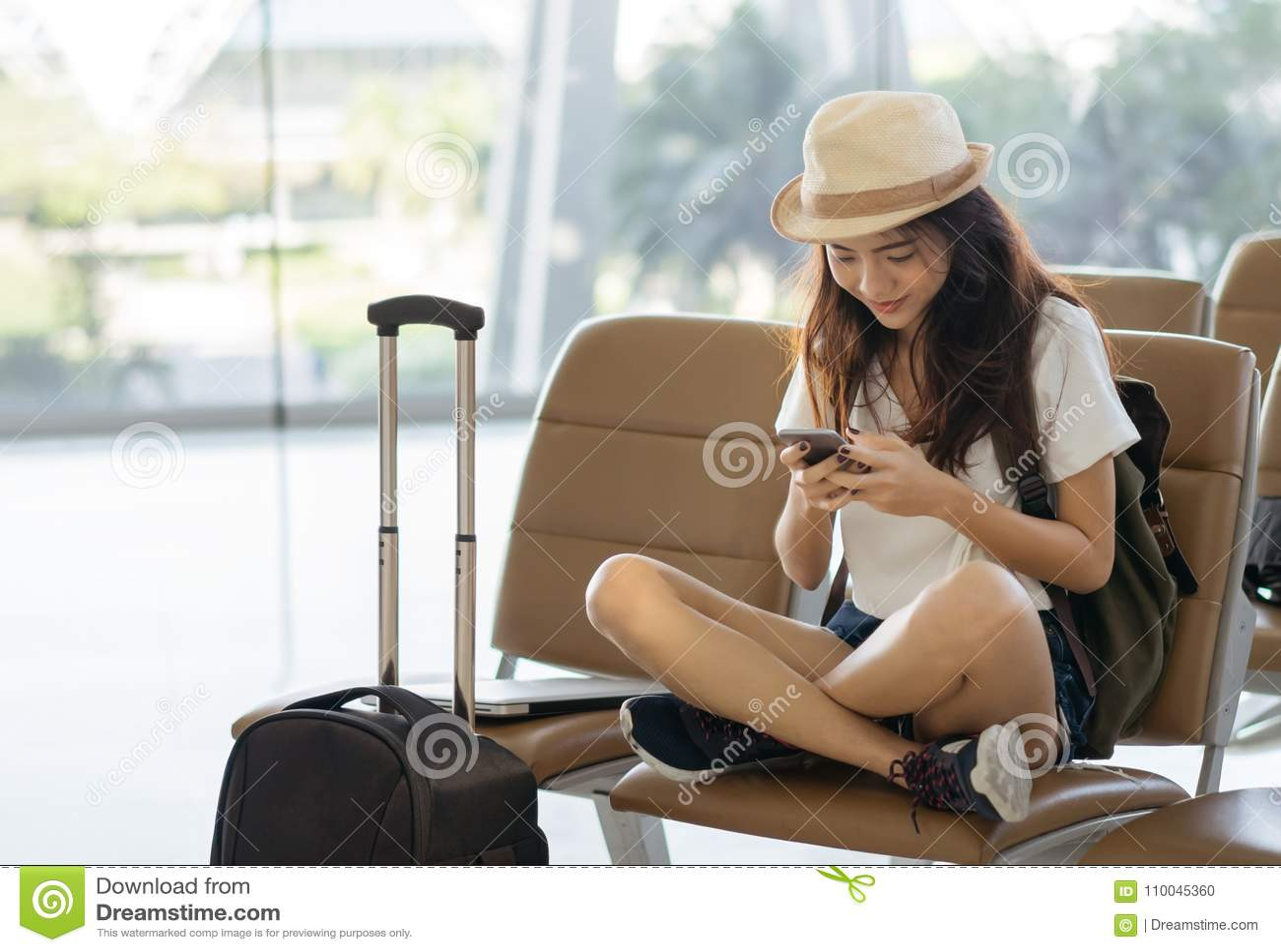 Adolescente asiático de la mujer que usa smartphone en el terminal de aeropuerto que se sienta con la maleta y la mochila del equ