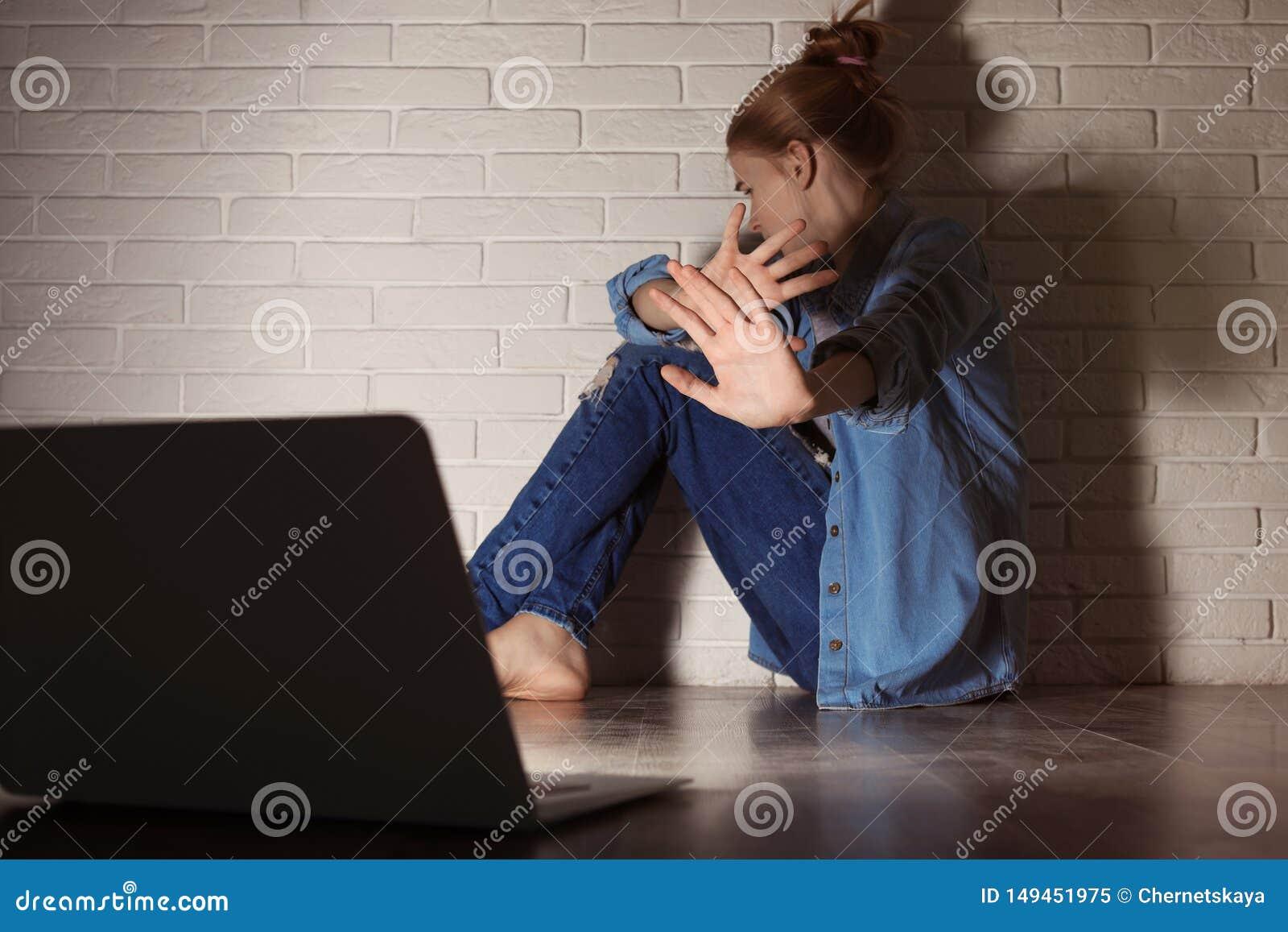 Adolescente assustado com o portátil no assoalho Perigo do Internet