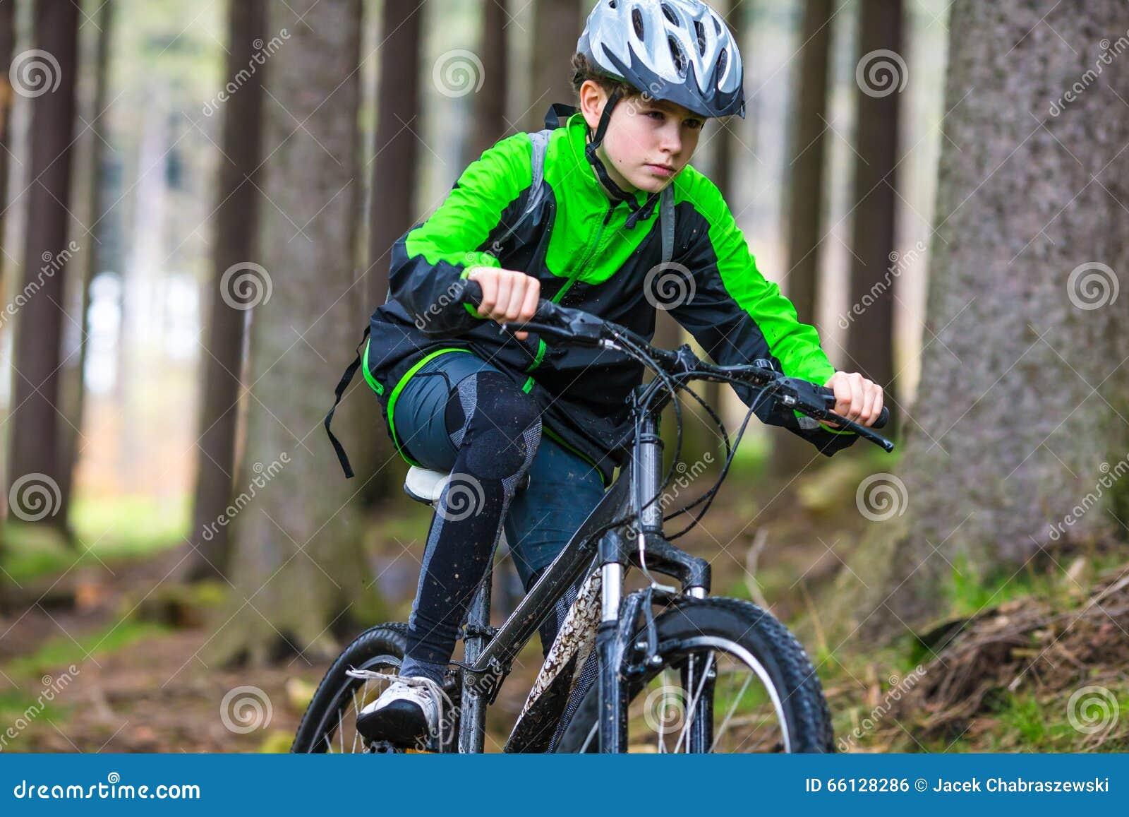 Adolescente biking en rastros del bosque