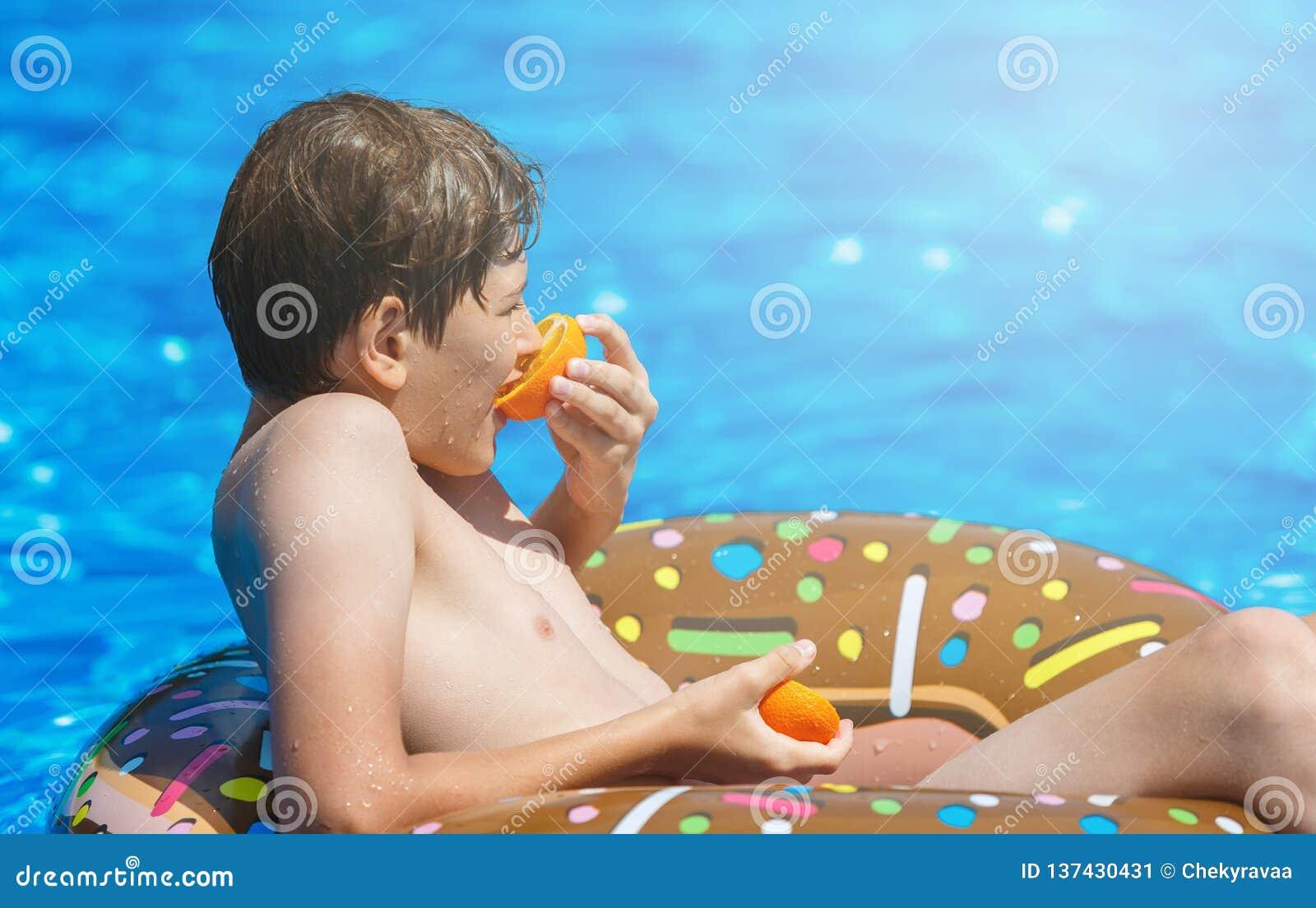 Adolescente bonito feliz do rapaz pequeno que encontra-se no anel inflável da filhós com a laranja na piscina Jogos ativos na águ
