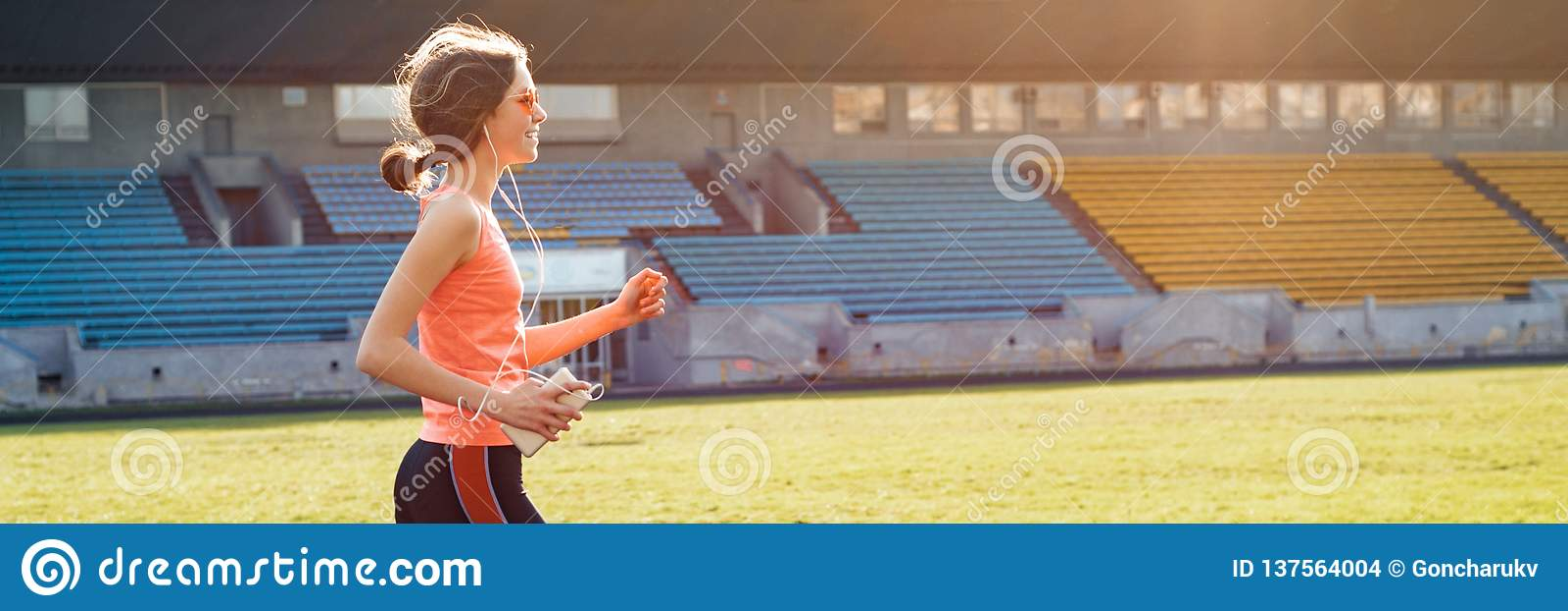 Adolescente bonito que corre no estádio, bandeira panorâmico