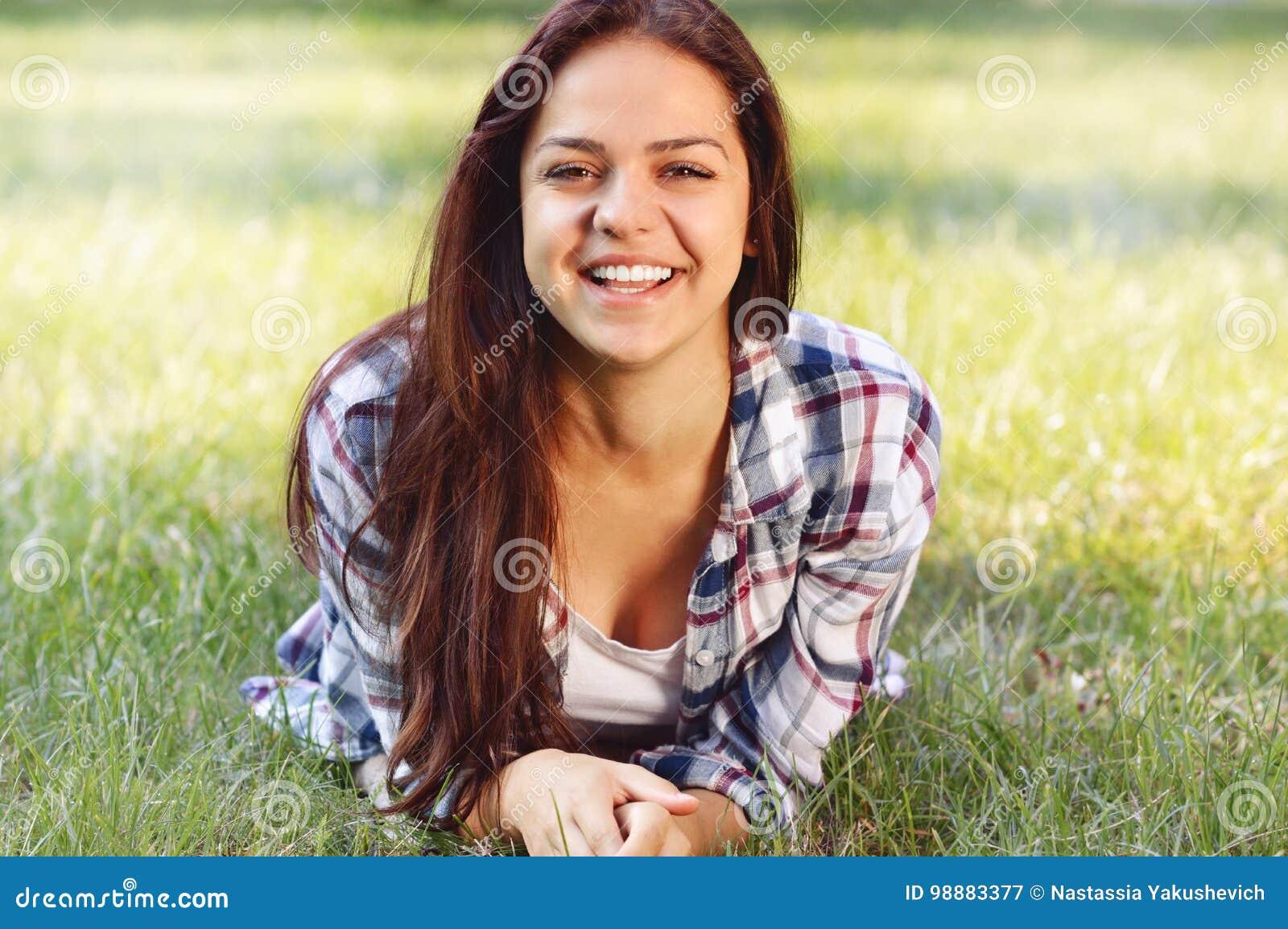 Adolescente bonito que encontra-se no campo da grama verde