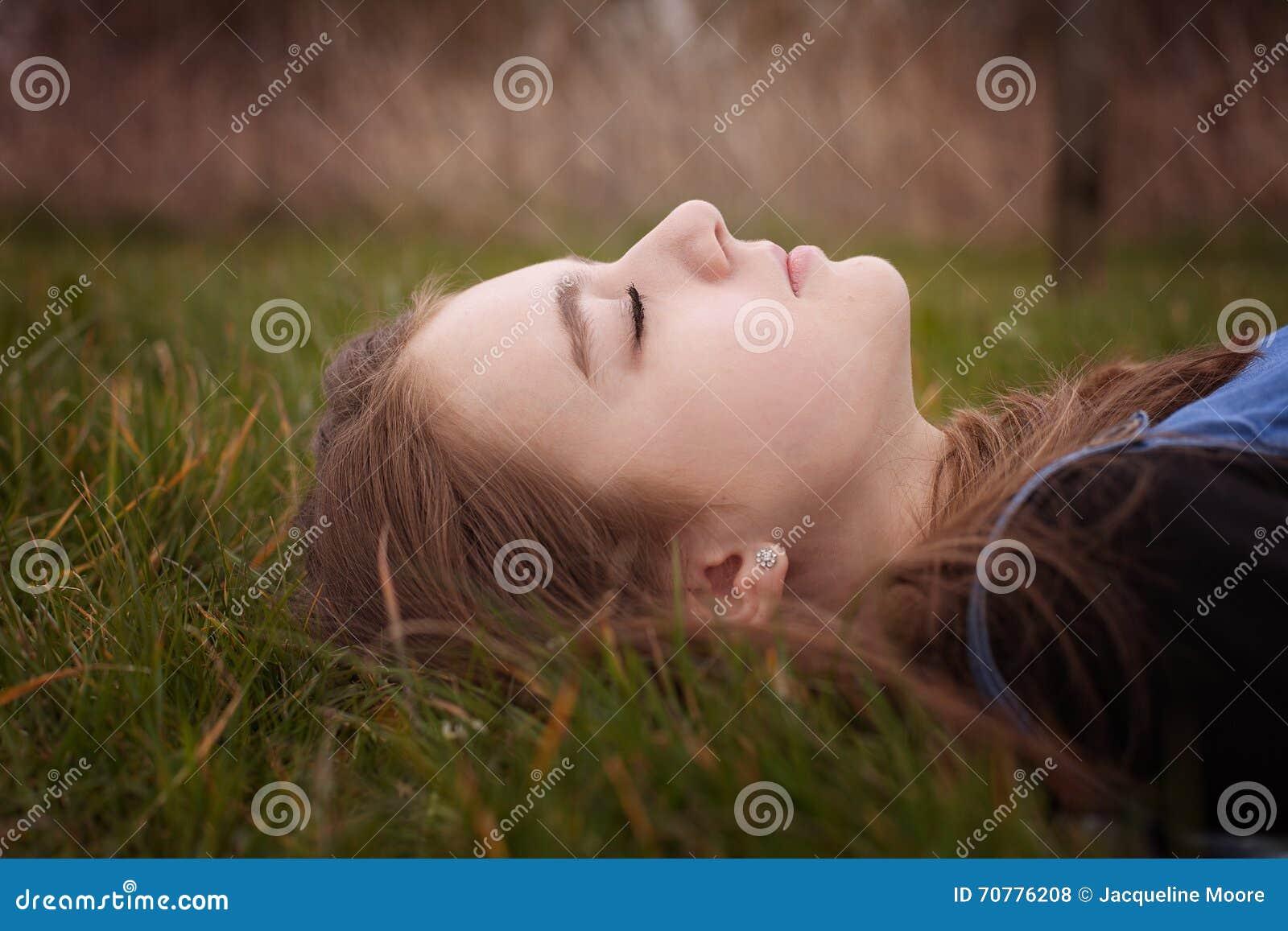 Adolescente bonito que encontra-se para baixo na grama com seus olhos fechados