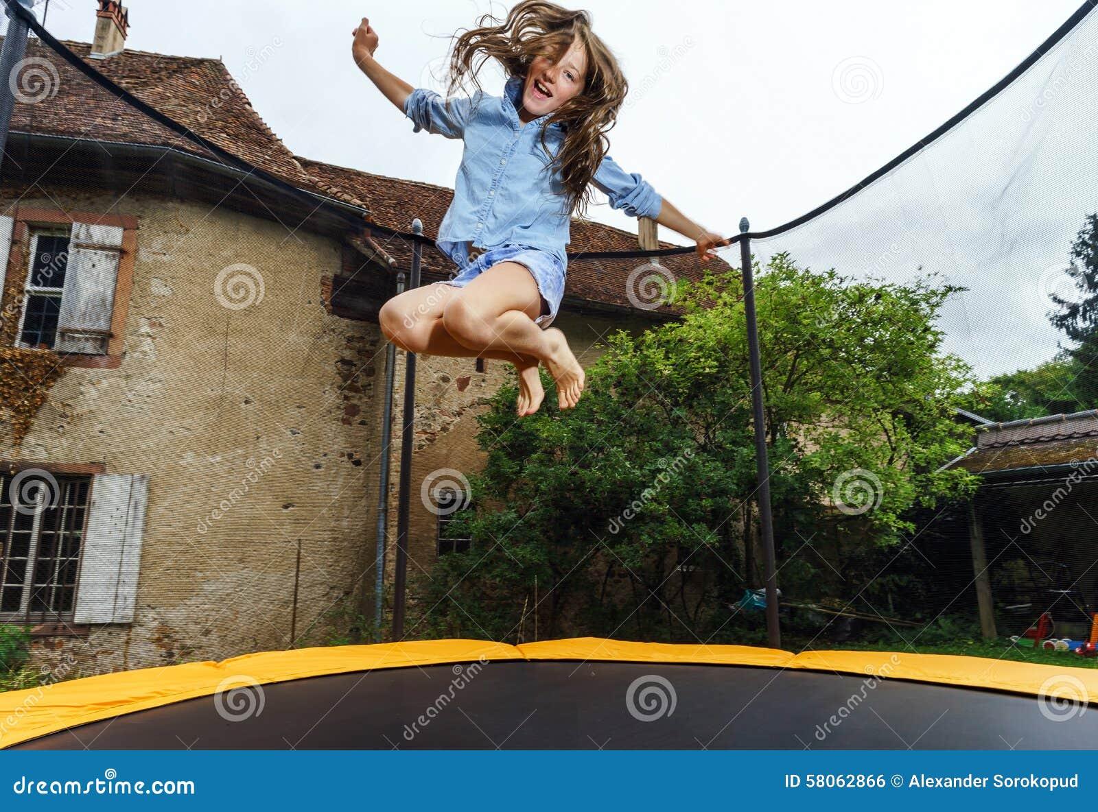 Adolescente bonito que salta no trampolim