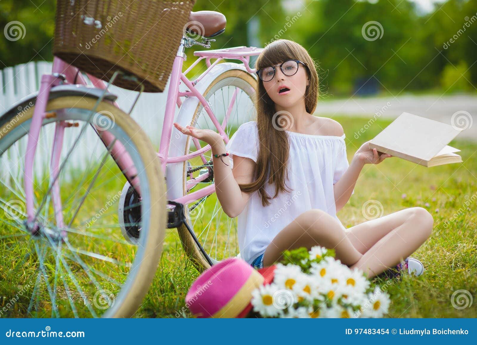 Adolescente che posa con la bicicletta su fondo del giardino