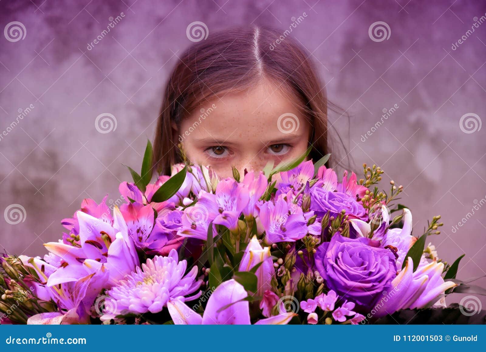 Adolescente com grande grupo de flores coloridas