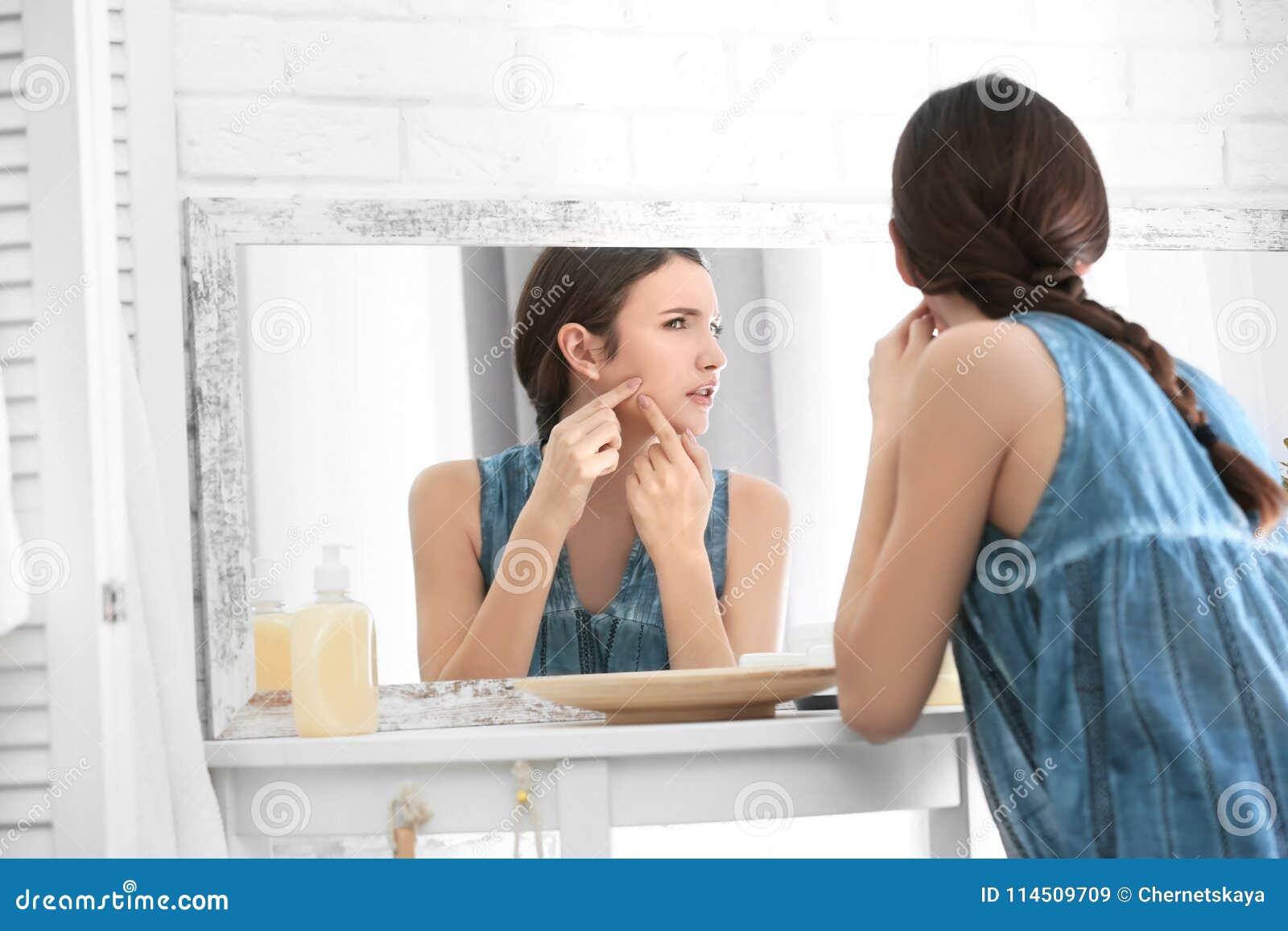 Adolescente com o problema da acne que olha no espelho