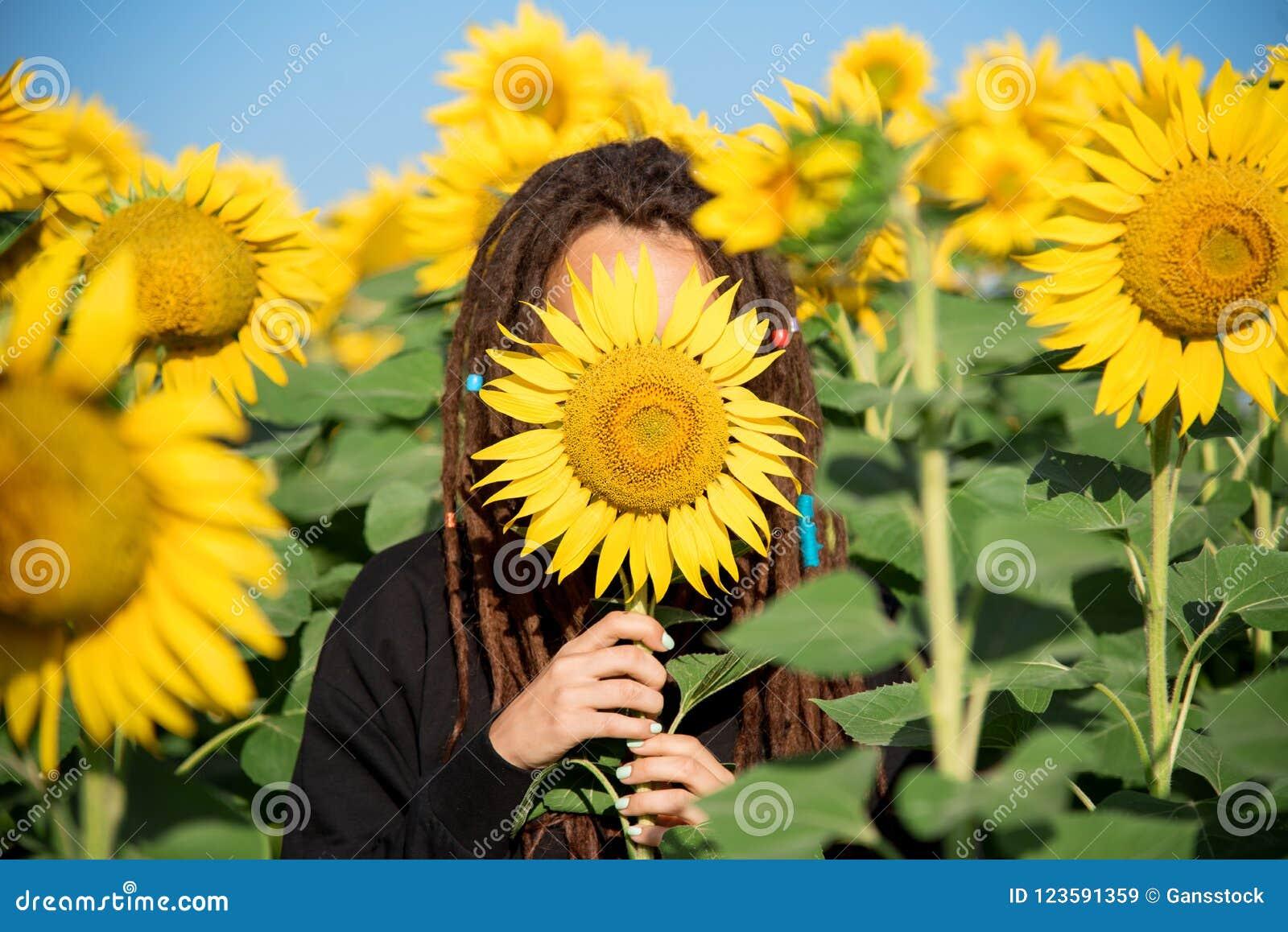 Adolescente con i dreadlocks che si nascondono nella mattina di estate in un campo con i girasoli