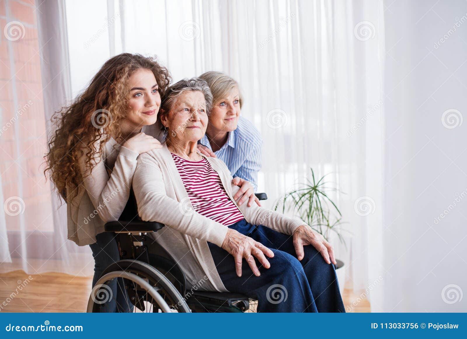 Adolescente con la madre y la abuela en wheelchiar en casa