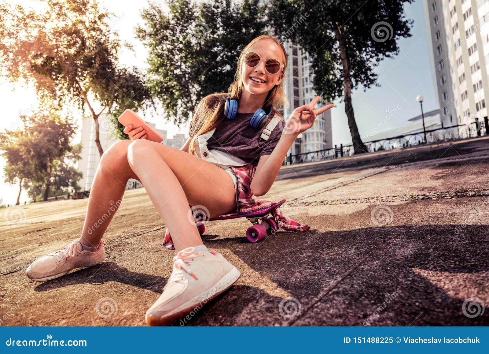 Adolescente dai capelli lunghi piacevole che mostra gesto di pace mentre sedendosi al sole