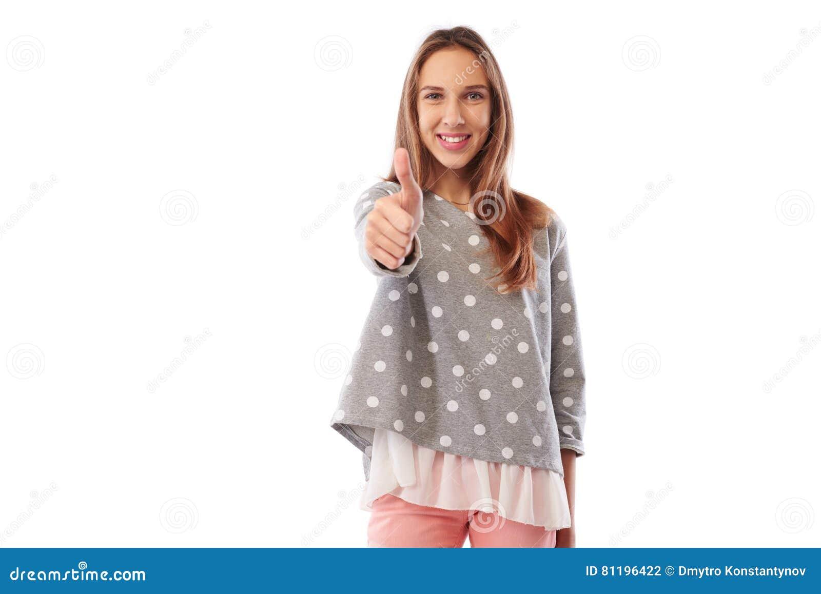 Adolescente de sorriso feliz que dá o polegar isolado acima no CCB branco