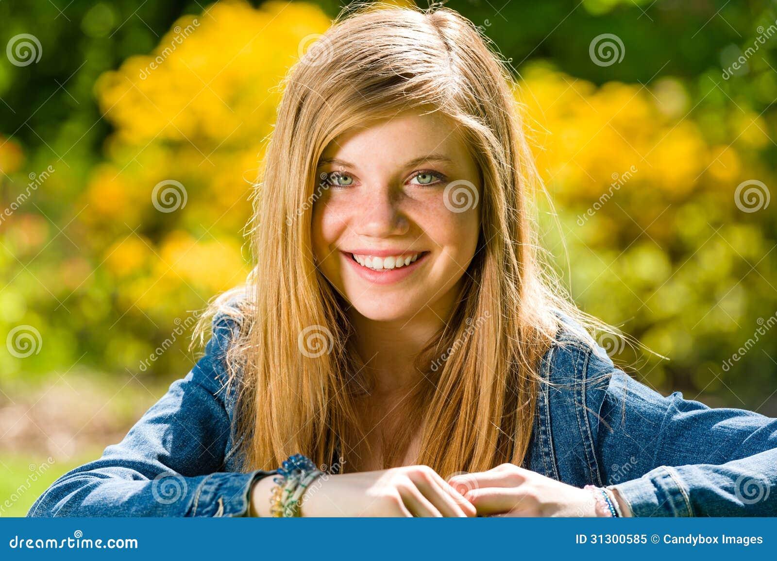 Adolescente de sorriso que olha a câmera fora