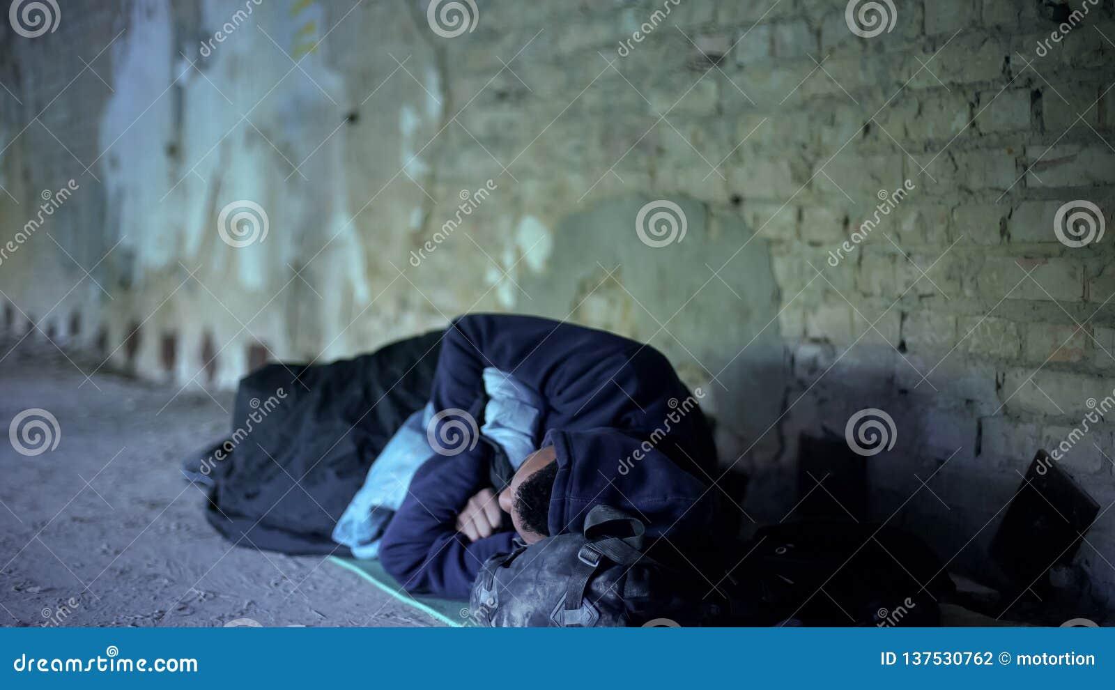 Adolescente desabrigado que dorme na rua, pobreza, sociedade egoísta indiferente