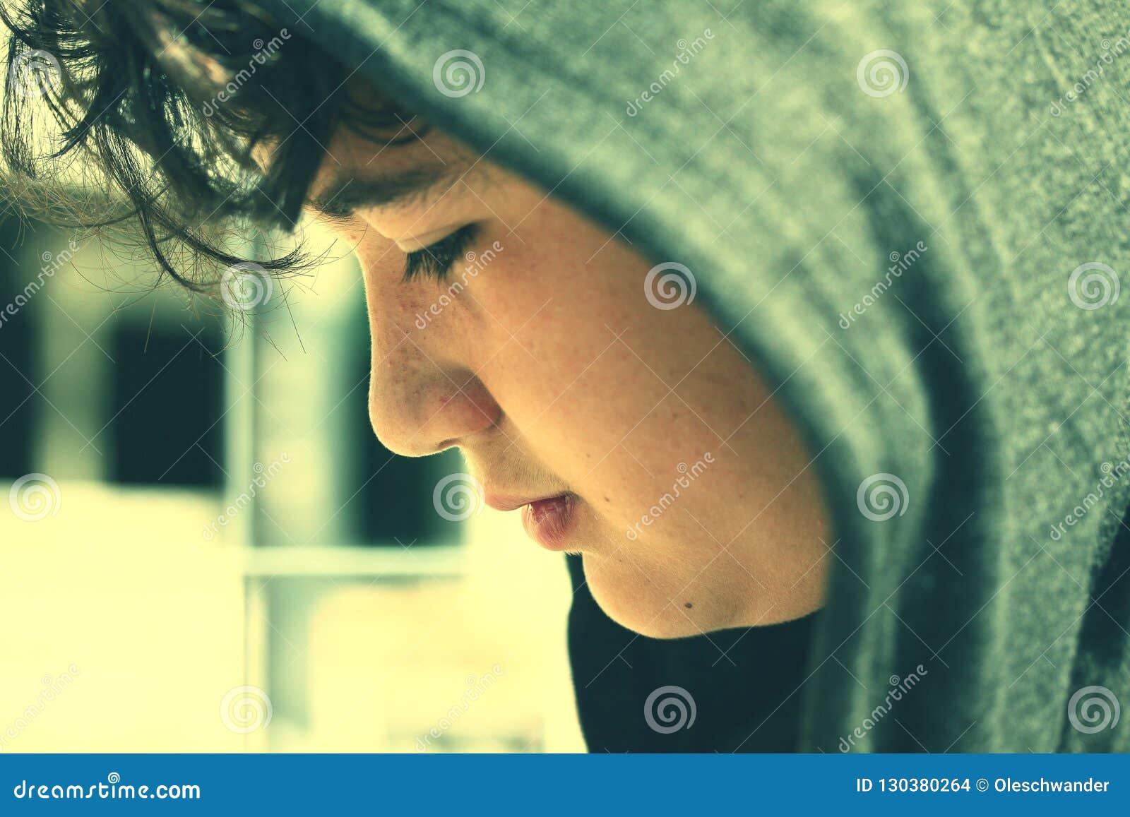 Adolescente disturbato triste del ragazzo di scuola che indossa un cappuccio - fine su nello stile istantaneo della foto con i co