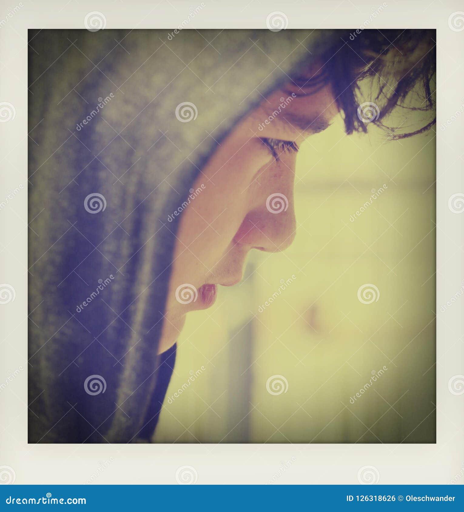 Adolescente disturbato triste del ragazzo di scuola che indossa una maglia con cappuccio che posa e che pensa nei suoi propri pen