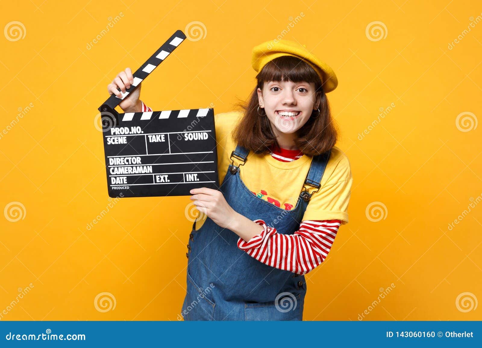 Adolescente divertido de la muchacha en la boina francesa, sundress del dril de algodón que sostienen clapperboard negro clásico