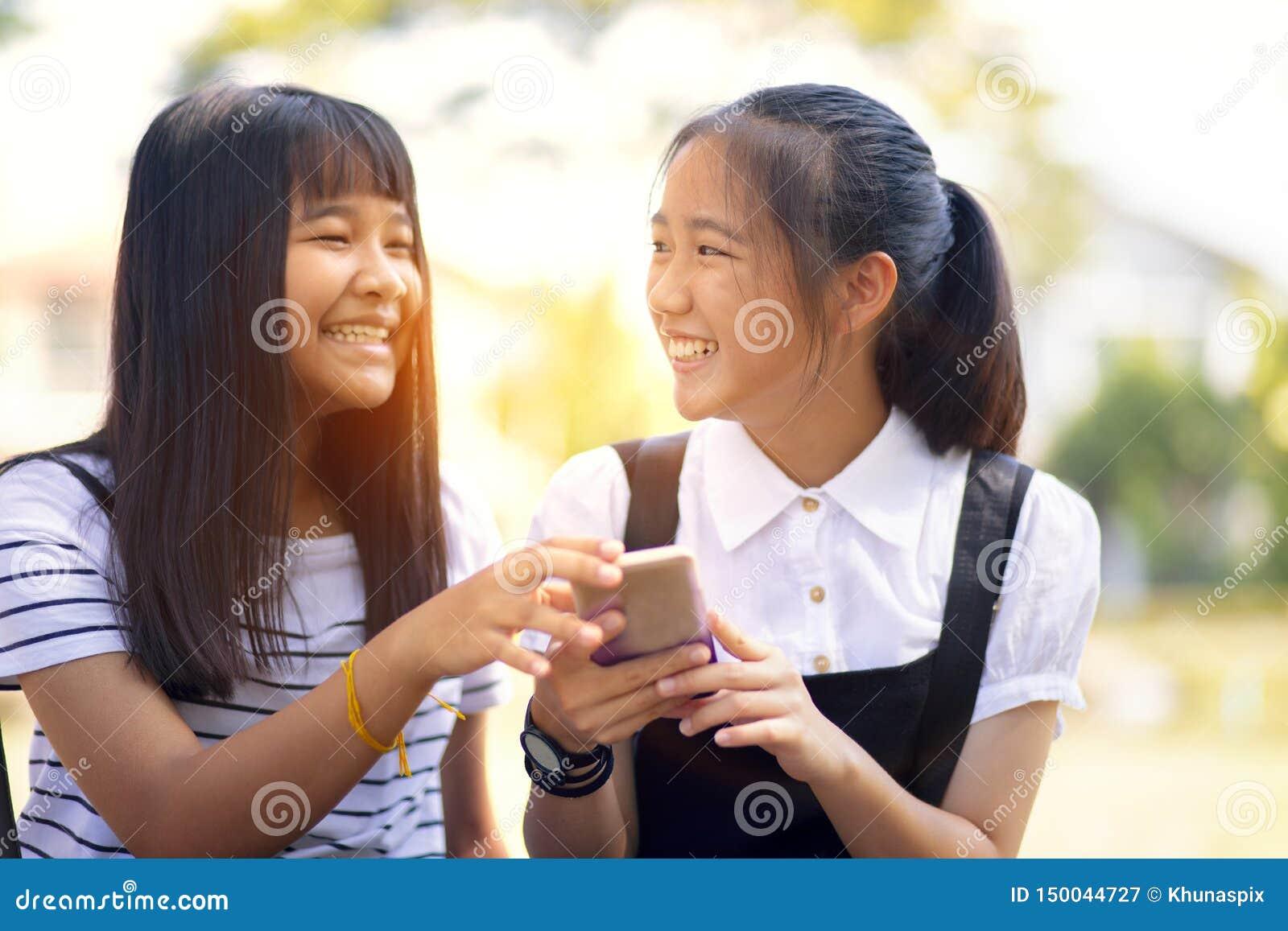 Adolescente dois asi?tico que ri com mensagem da leitura da cara da felicidade na tela esperta do telefone