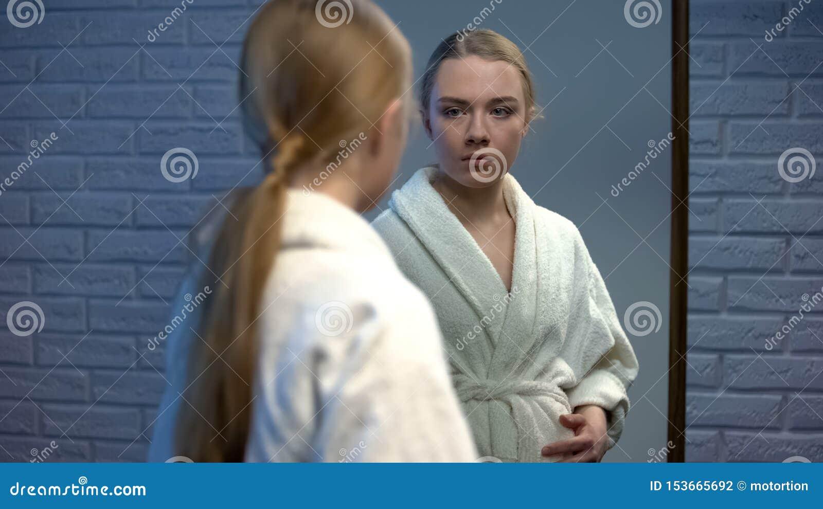 Adolescente effrayée tenant le ventre enceinte regardant dans le miroir, irresponsabilité