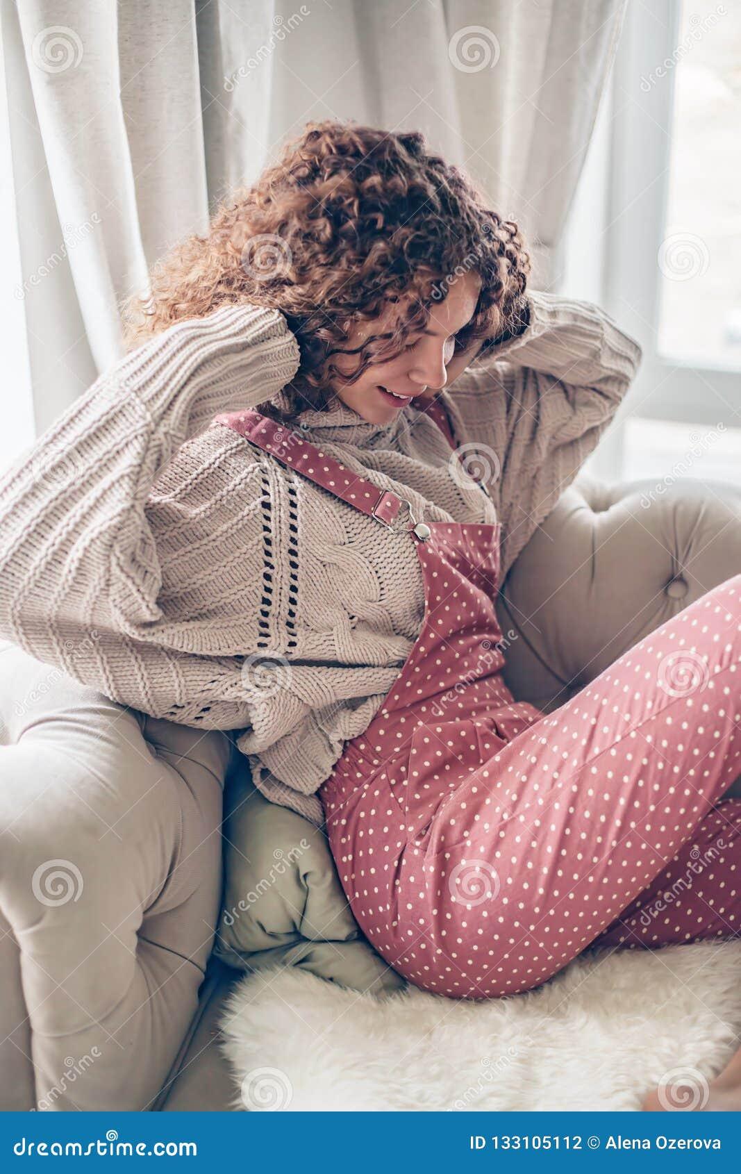 Adolescente en suéter y mono en un sofá