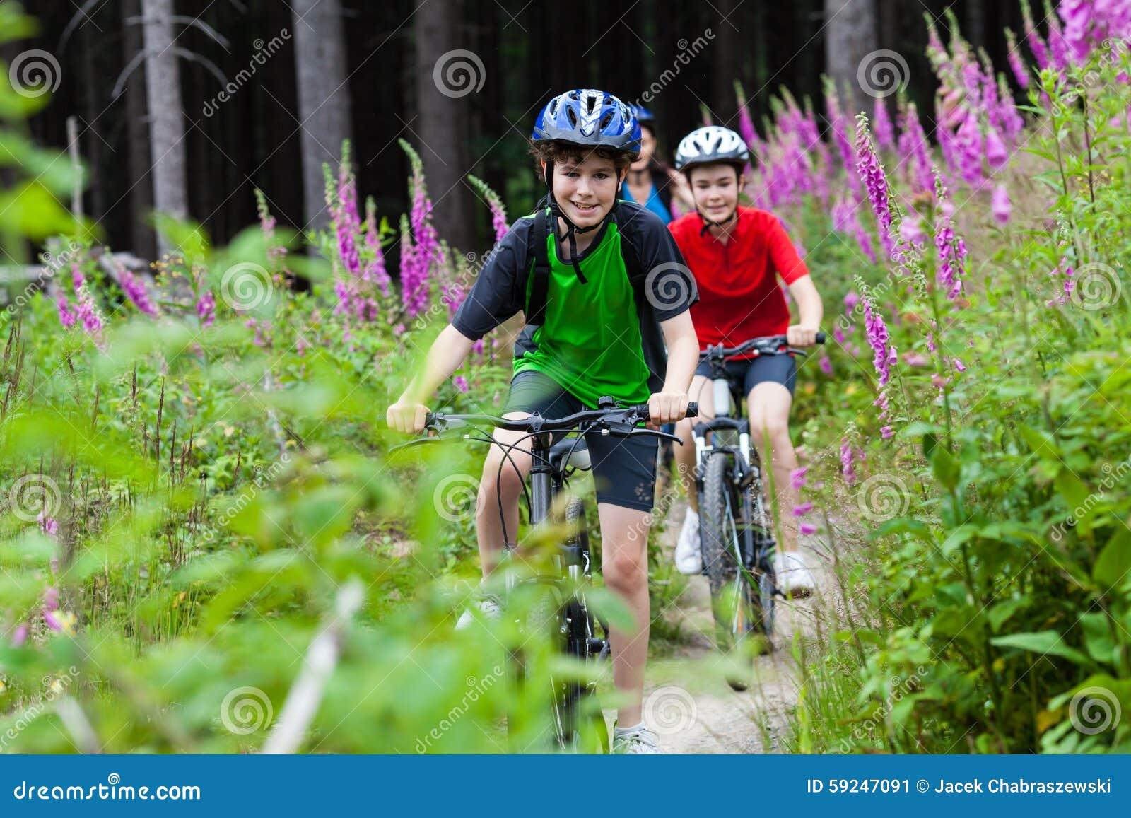 Adolescente et garçon faisant du vélo sur des traînées de forêt
