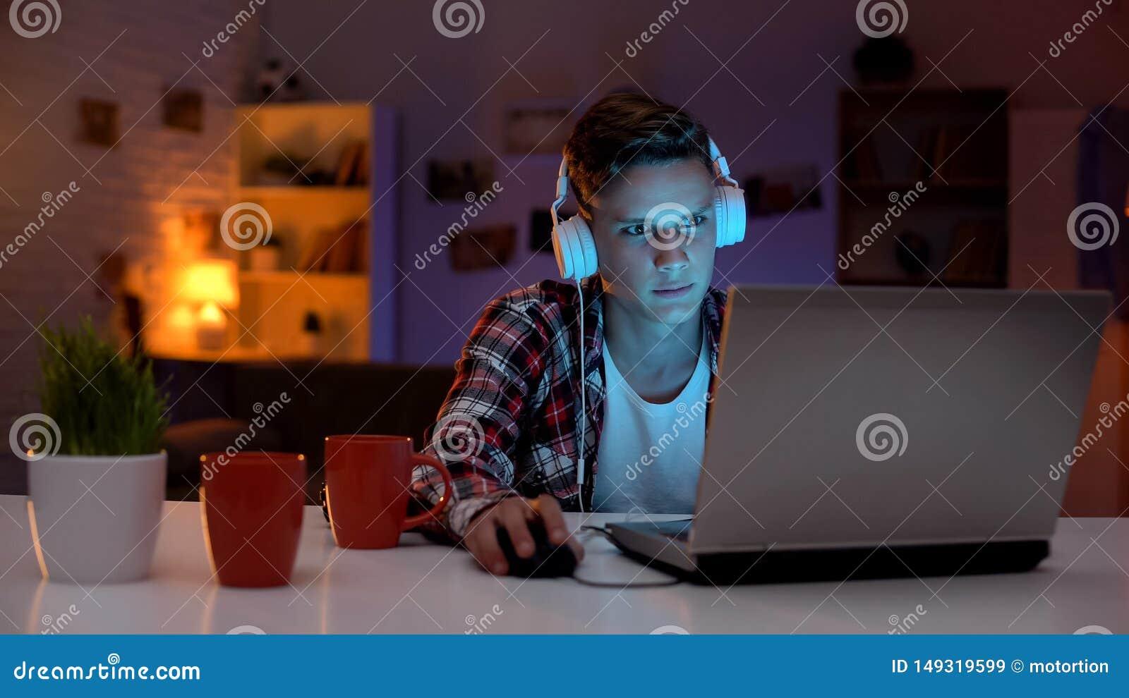 Adolescente extremamente ansioso que joga o jogo de computador em emo??es descontroladas do port?til