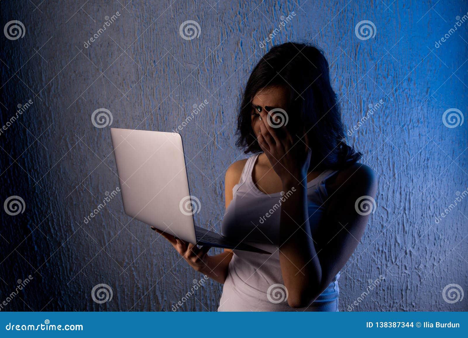 Adolescente fêmea triste e assustado com cyberbullying e a perseguição do sofrimento do portátil do computador que são sentimento