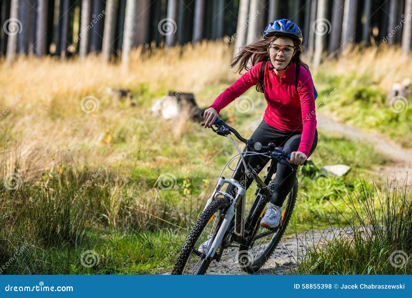 Adolescente faisant du vélo sur des traînées de forêt