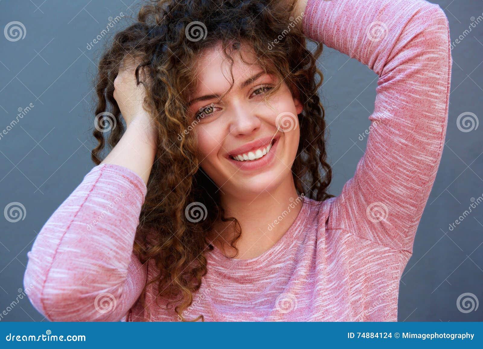 Adolescente feliz com mãos no cabelo