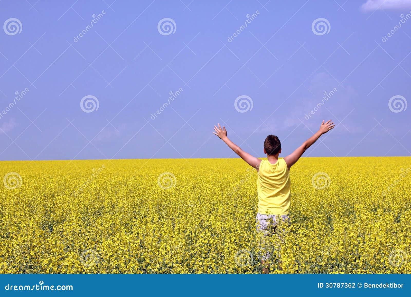 Adolescente feliz que se coloca en un campo de la violación de semilla oleaginosa