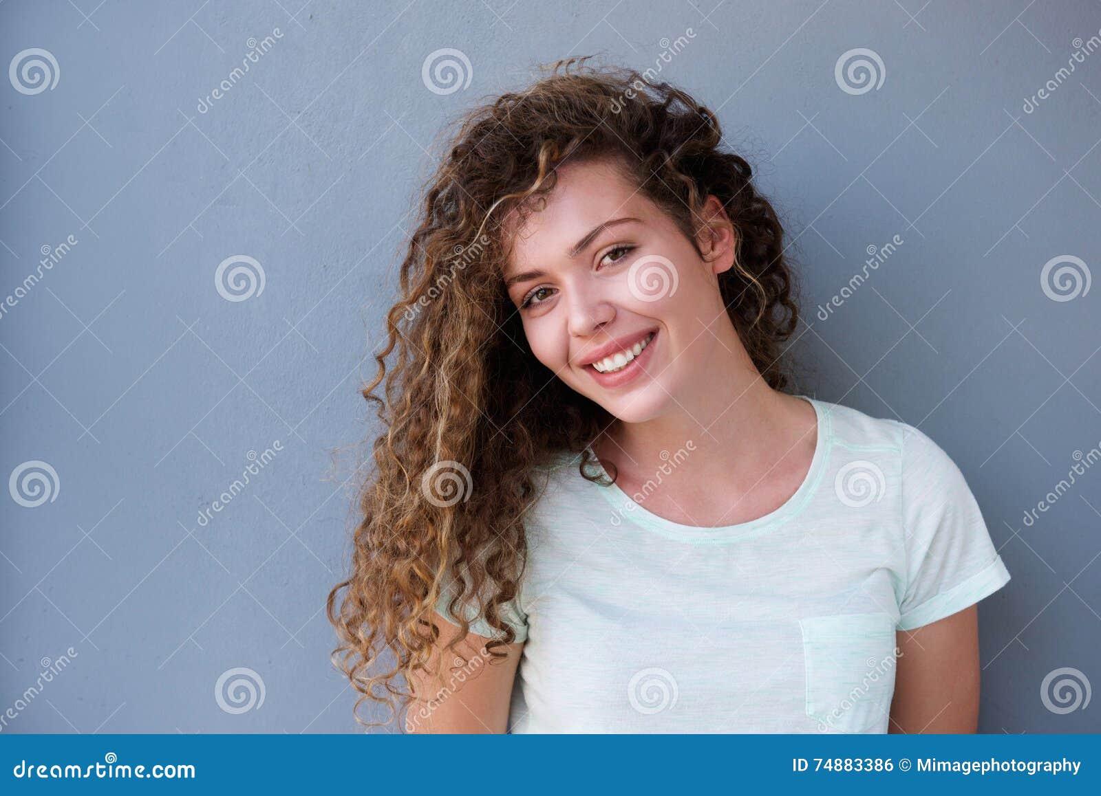 Adolescente feliz que sorri contra a parede cinzenta
