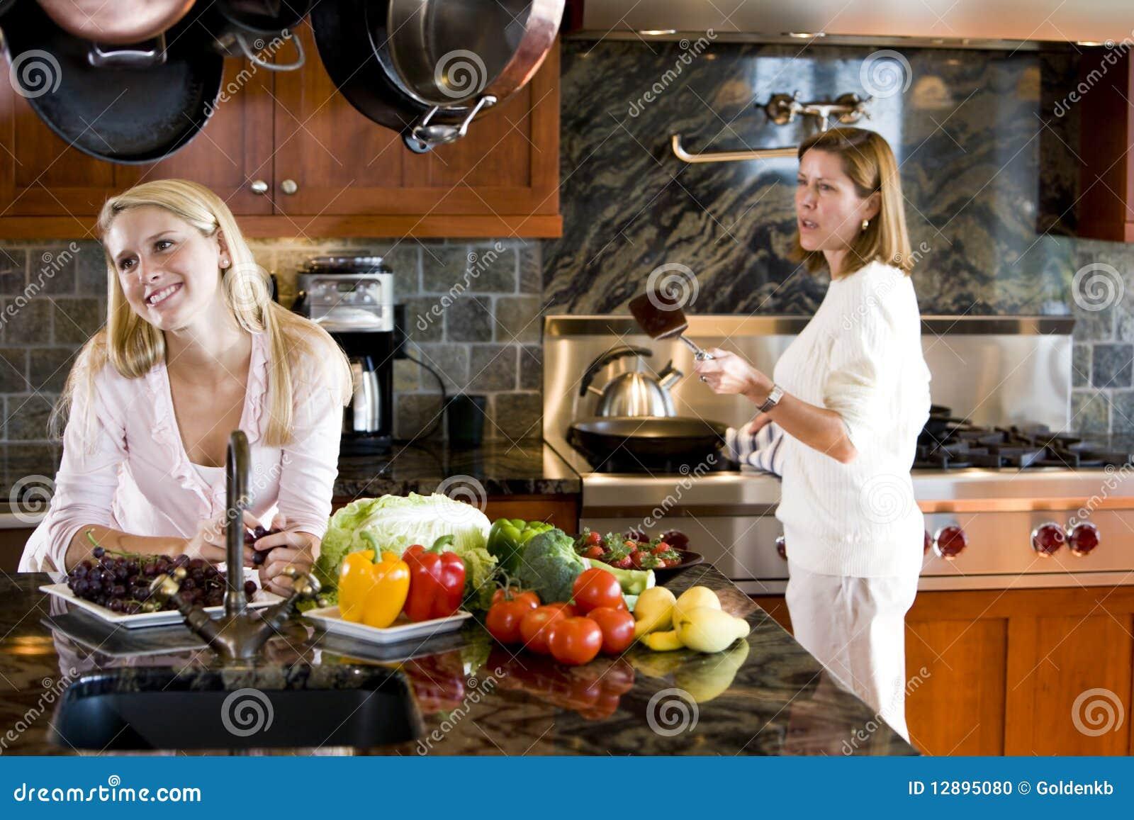 Adolescente heureuse dans la cuisine avec la mère