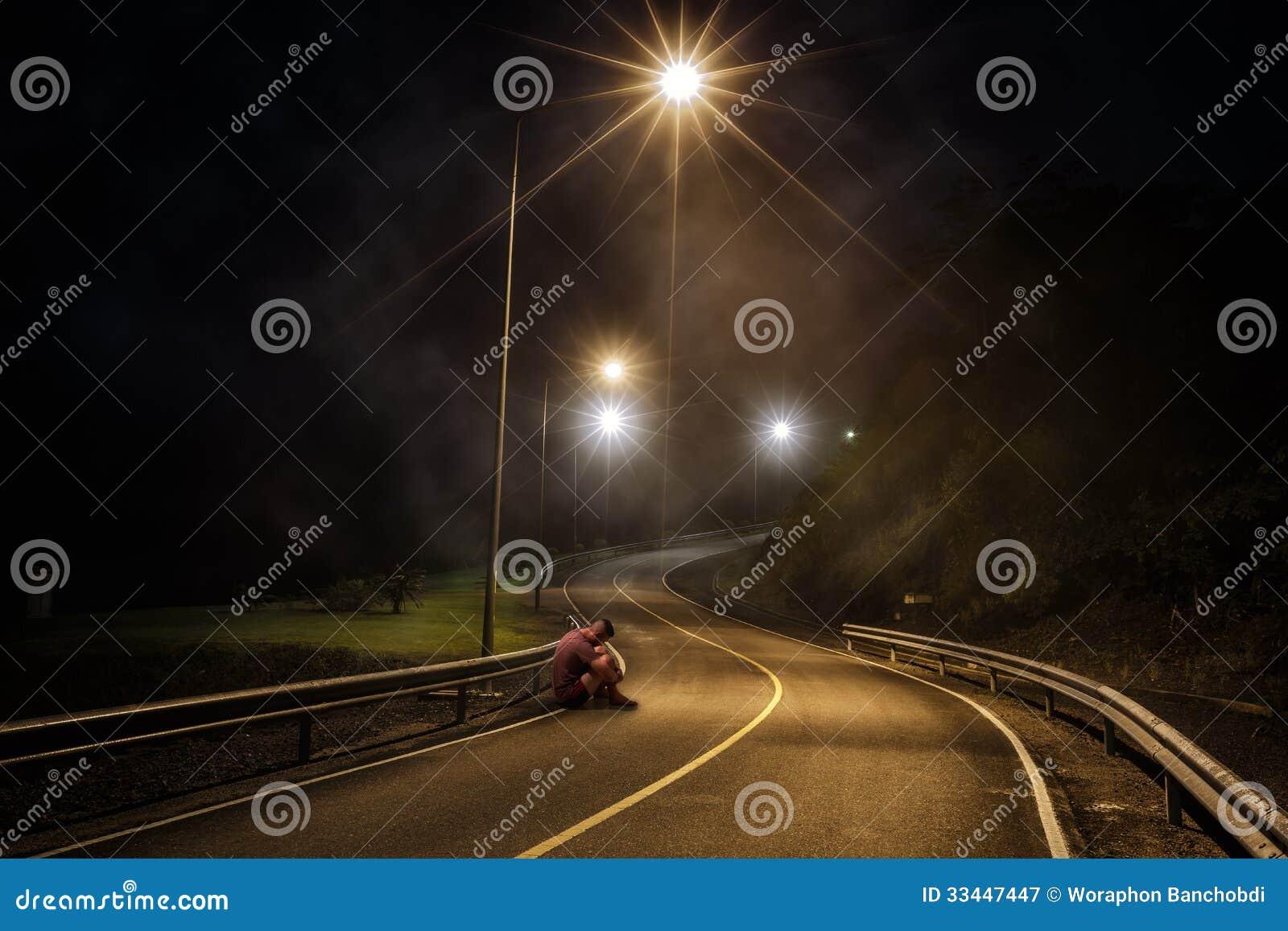 Adolescente incomodado com a cara escondida que senta-se na rua da noite