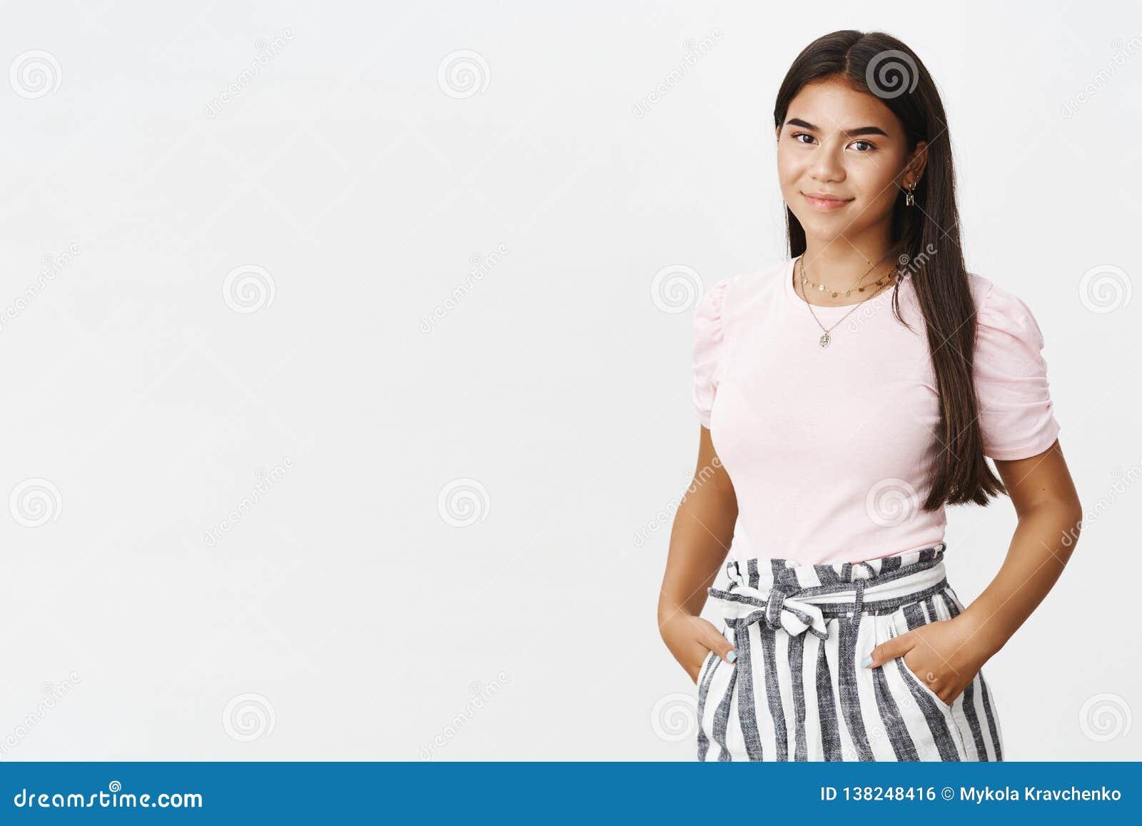 Adolescente indiano encantador agradável bonito à moda e do hapyp nas calças e no t-shirt que guardam as mãos no sorriso dos bols