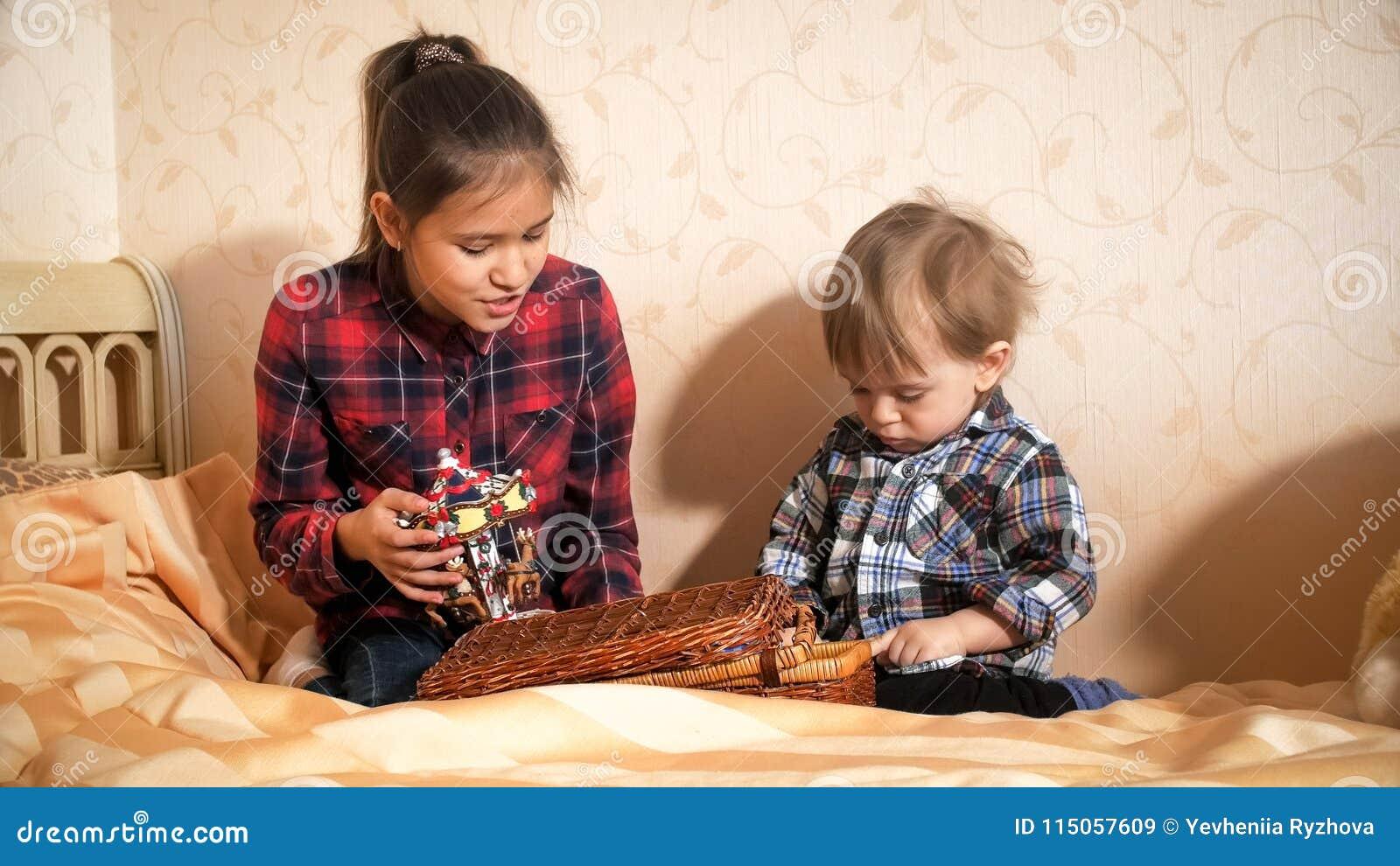 Adolescente jouant avec son frère d enfant en bas âge sur le lit à la chambre à coucher