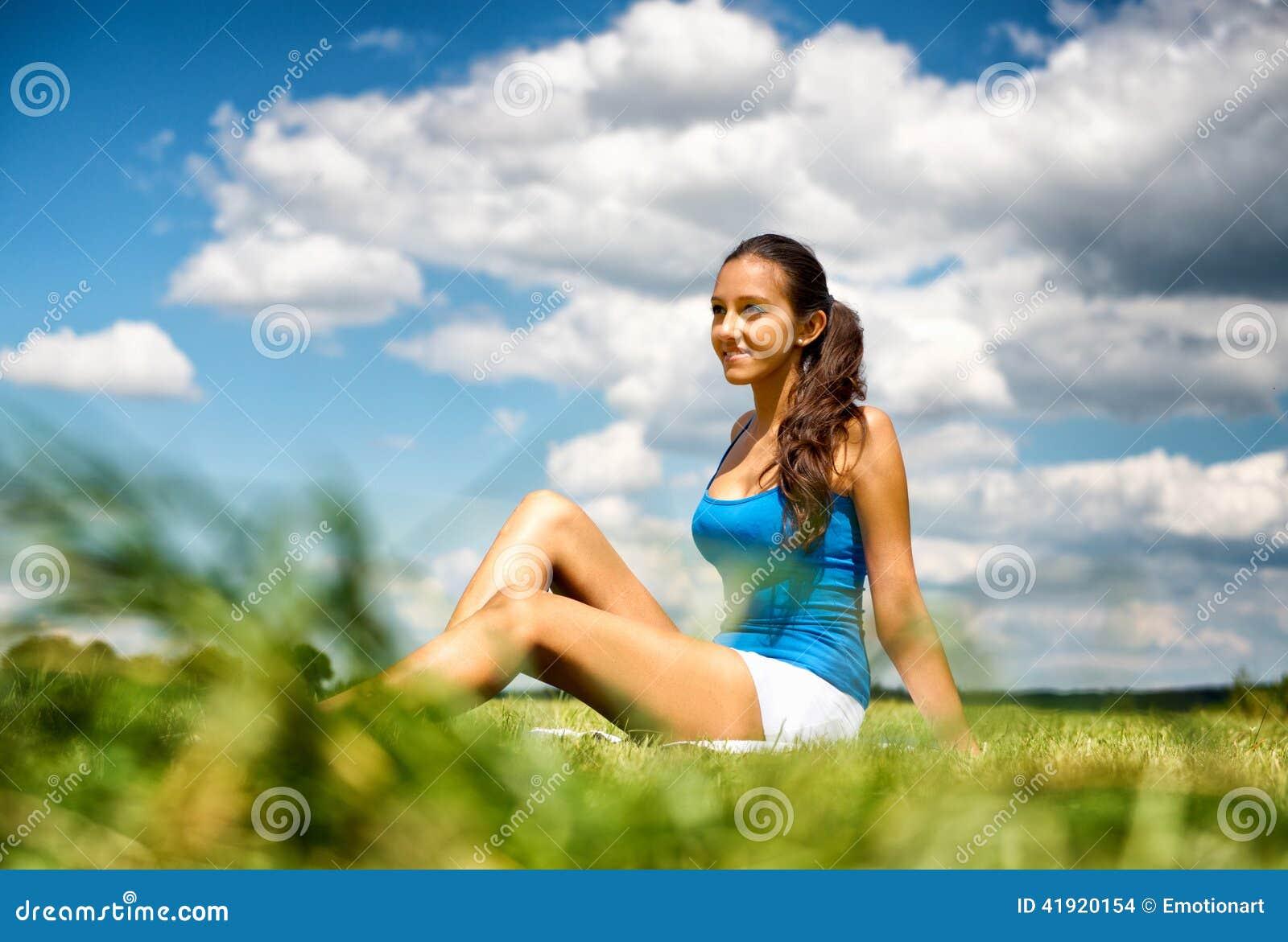 Adolescente joven amistoso sonriente en un campo