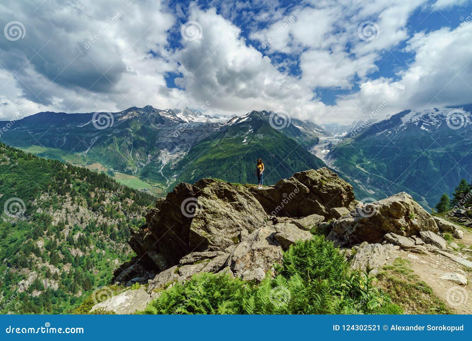 Adolescente joven que presenta en piedra grande en las montañas