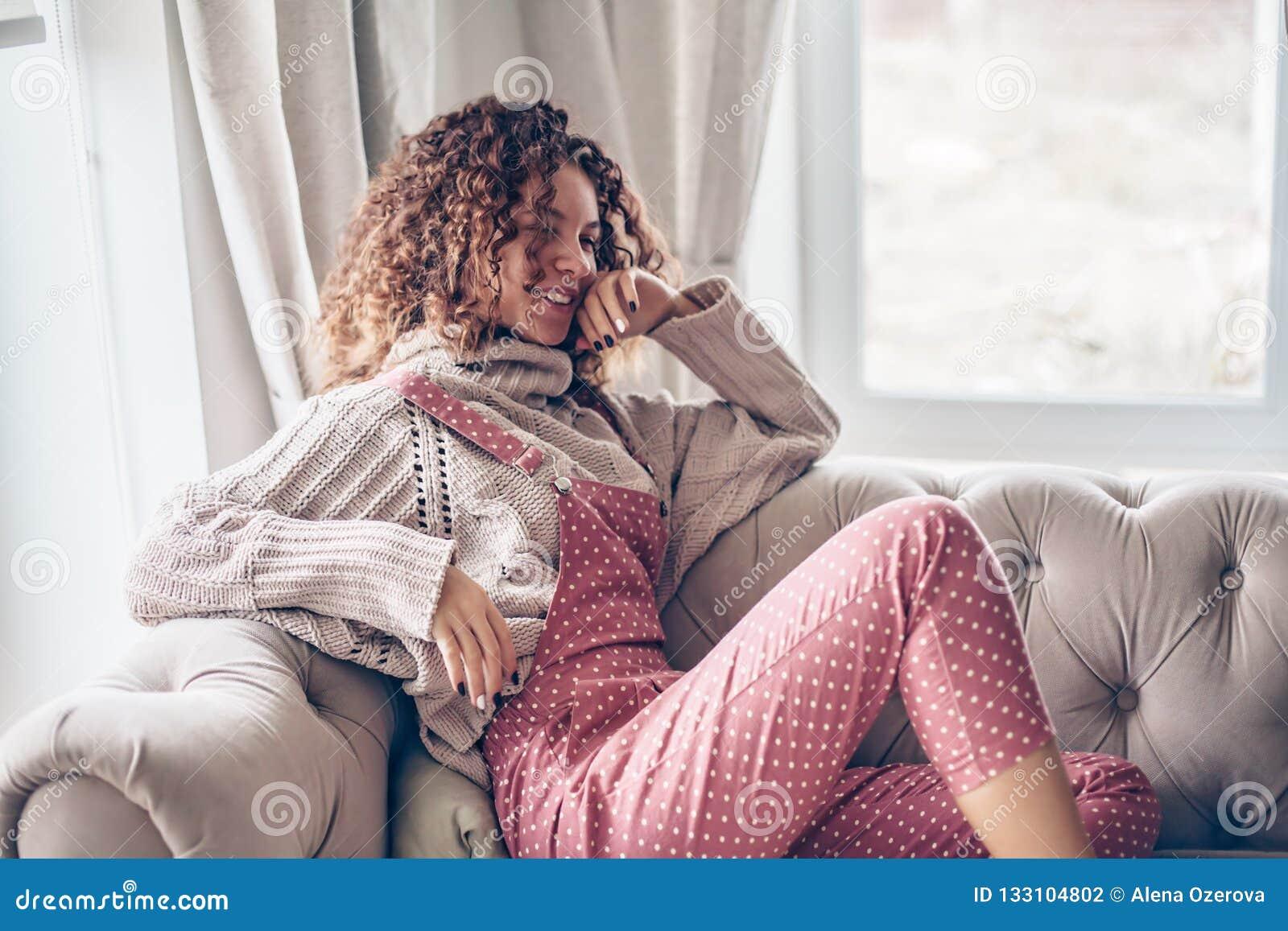 Adolescente na camiseta e no fato-macaco em um sofá