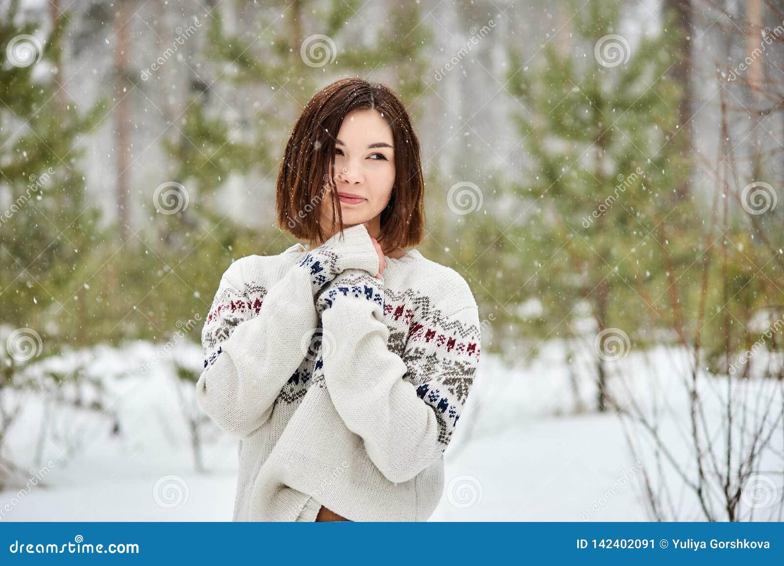 Adolescente na queda de neve da floresta do inverno
