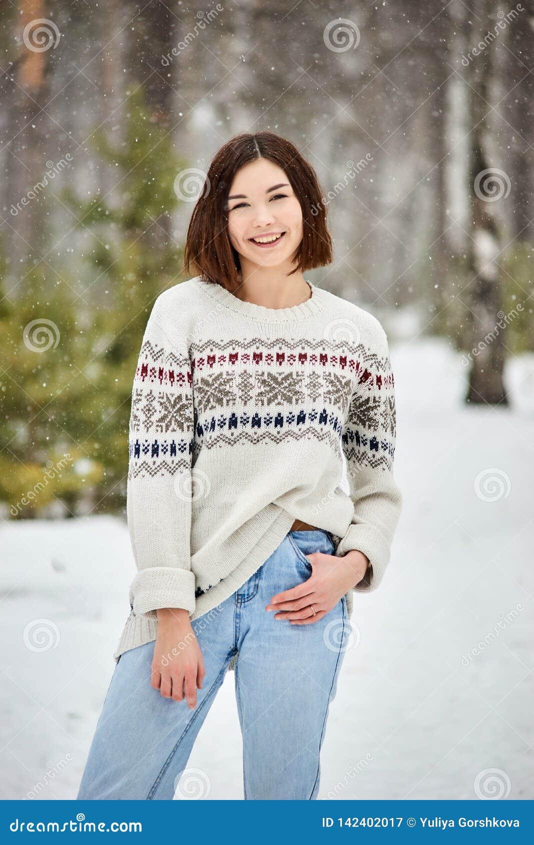 Adolescente nelle precipitazioni nevose della foresta di inverno