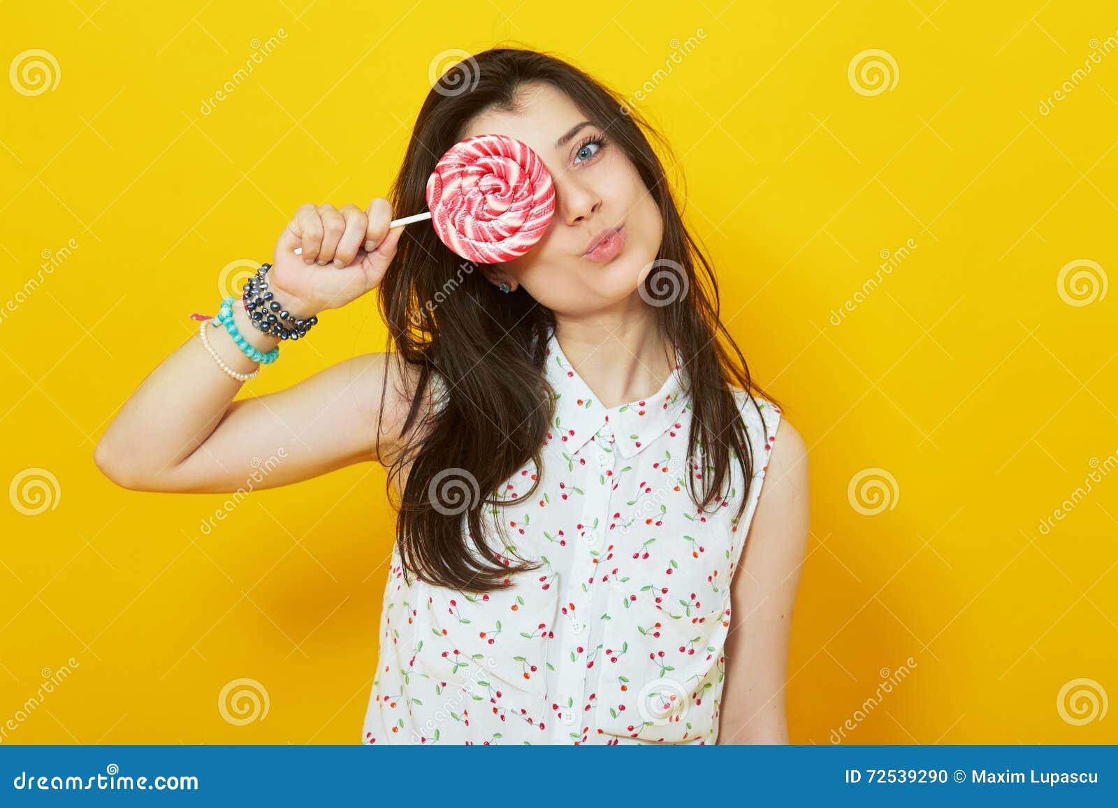 Adolescente no fundo amarelo vívido brilhante que guarda o pirulito