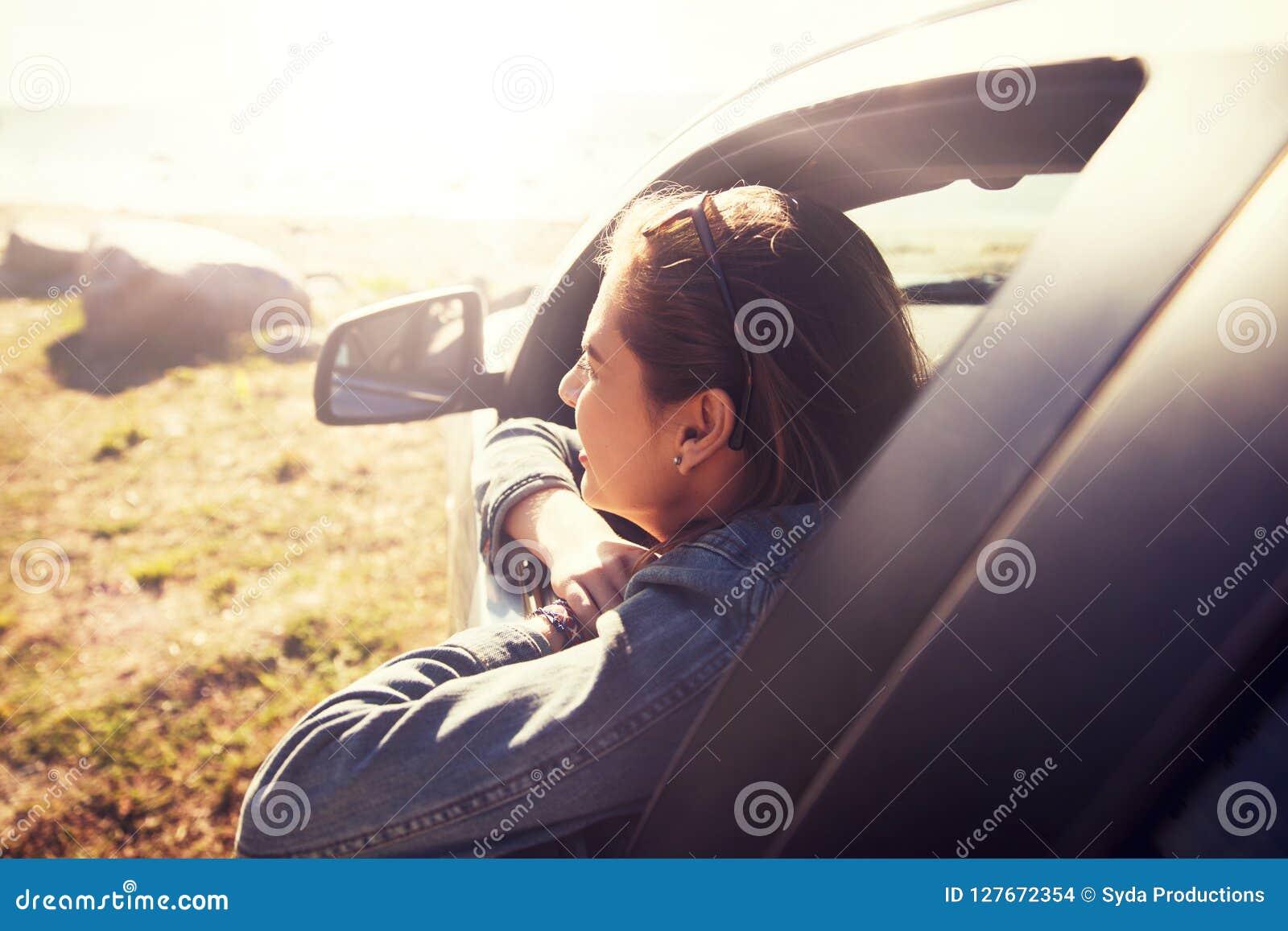 Adolescente ou jeune femme heureuse dans la voiture