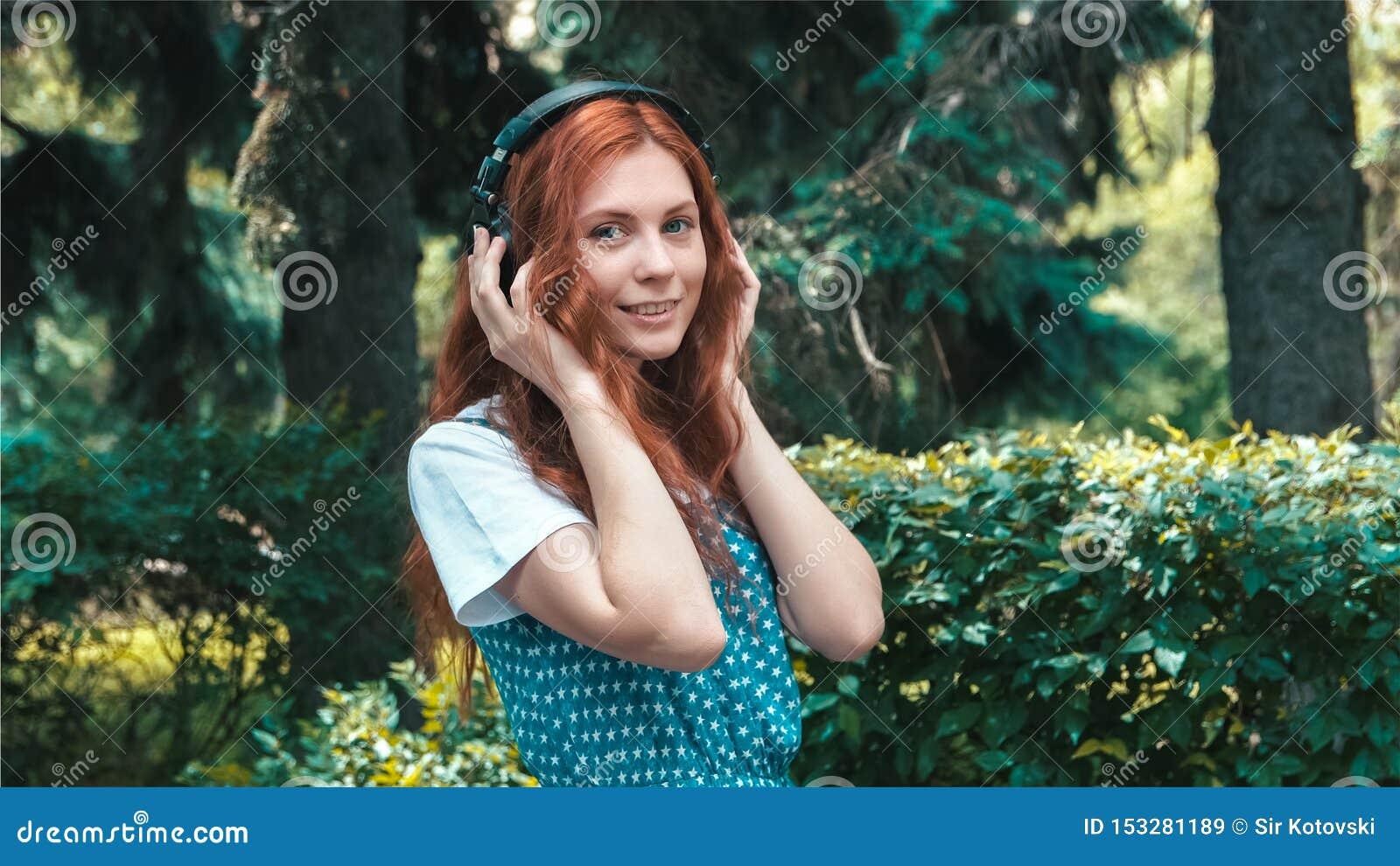 Adolescente pelirrojo pecoso escuchar música en auriculares grandes