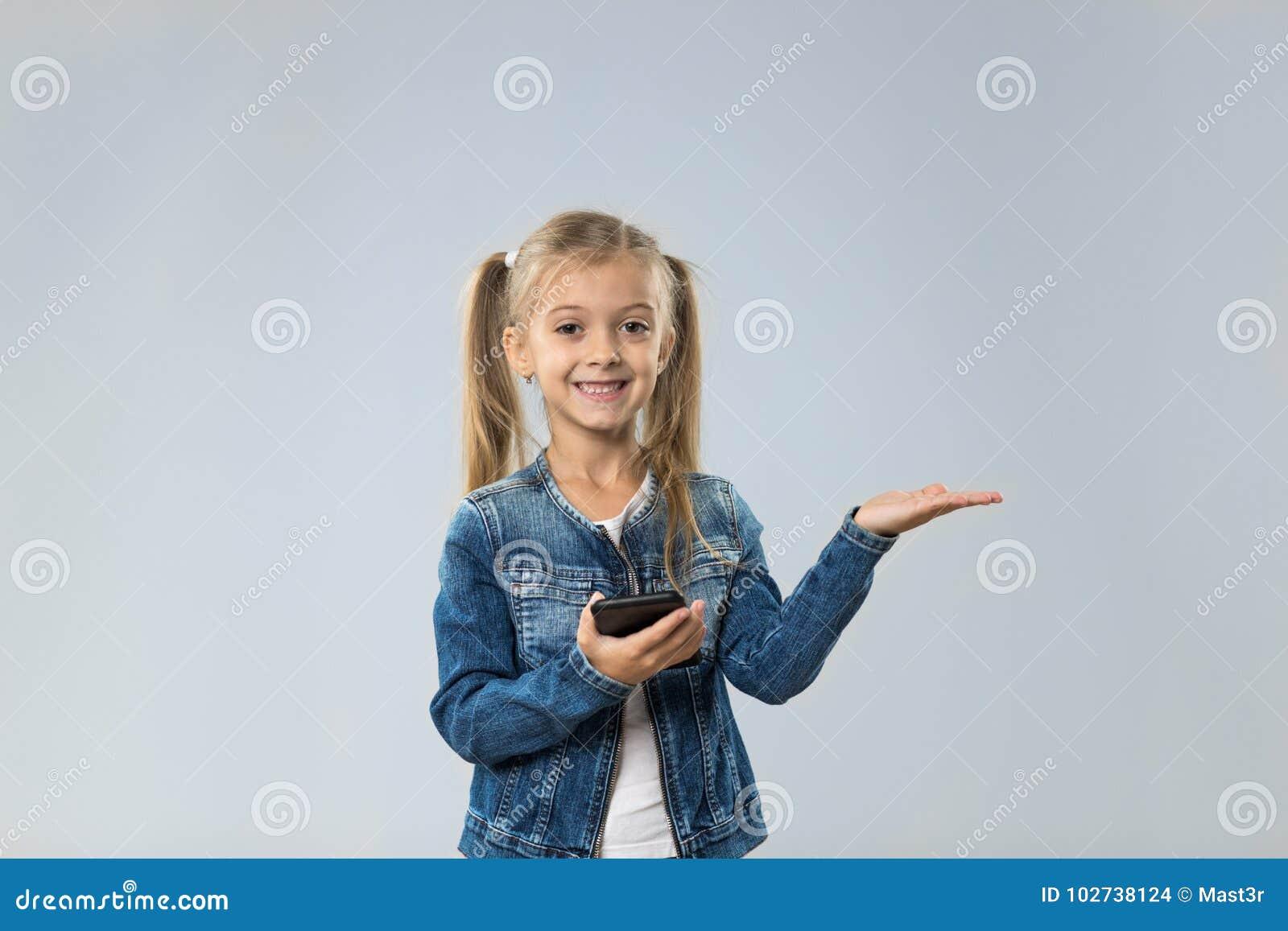 Adolescente pequeno que usa o telefone esperto da pilha, palma aberta de sorriso feliz pequena da criança ao espaço da cópia