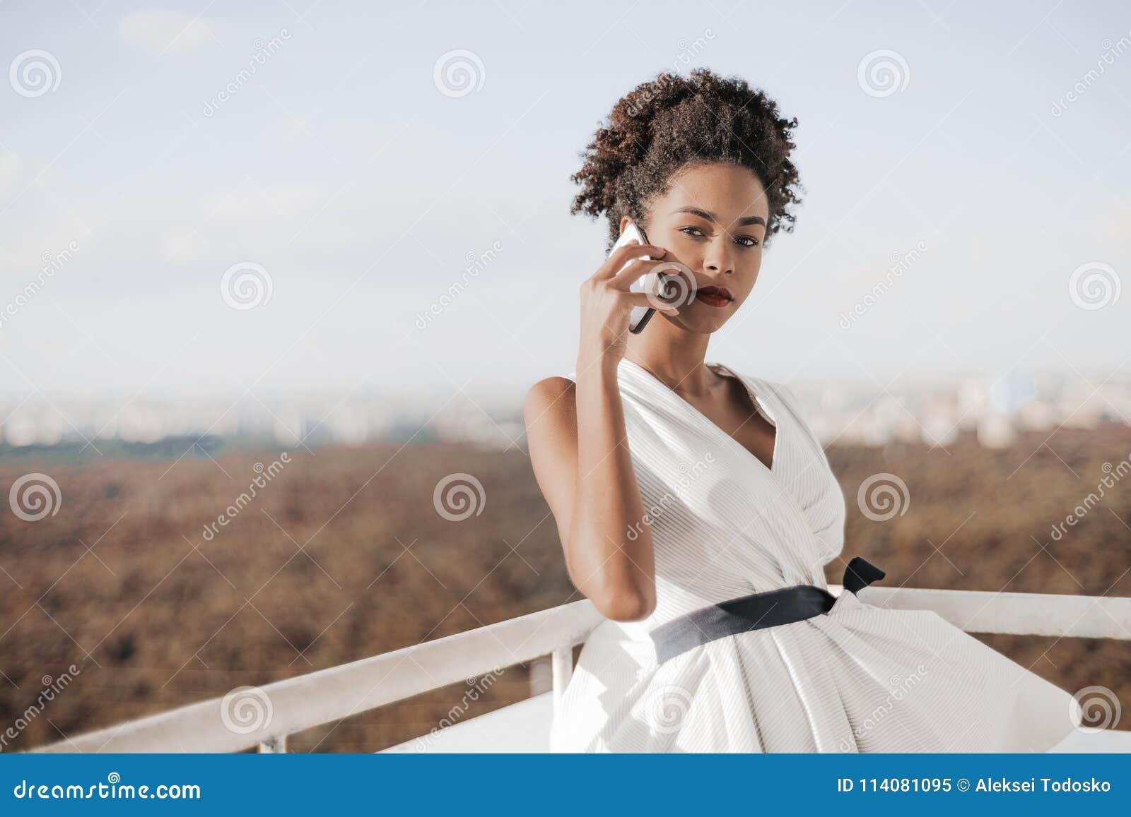 Adolescente preto que fala no smarthpone no balcão do arranha-céus